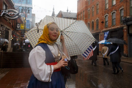 Sophia Zervious of Northville holds her umbrella during the annual Greece Independence Day Parade on Sunday in Detroit.