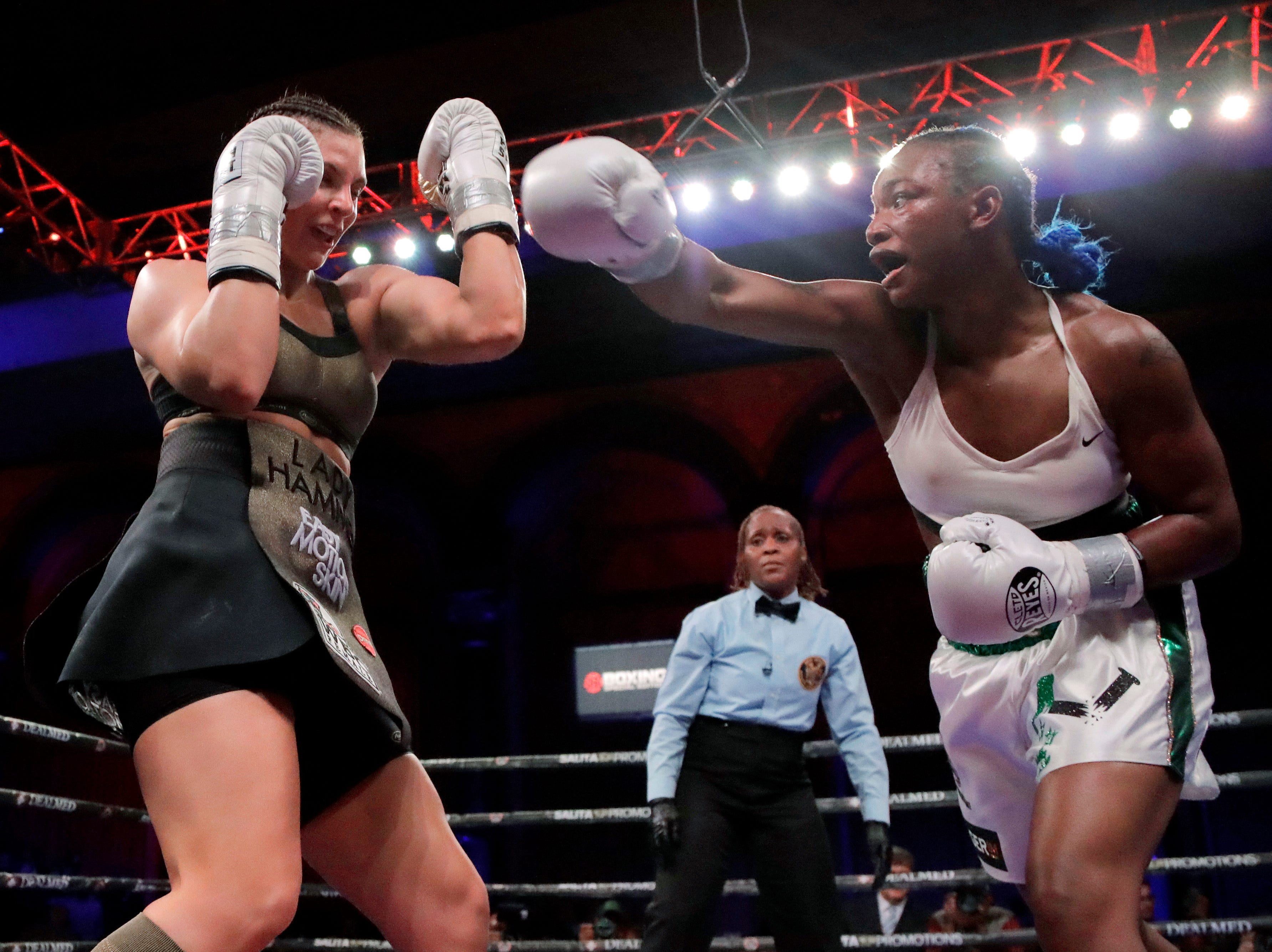 Claressa Shields, right, throws a right at Christina Hammer during fourth the round of the women's middleweight championship boxing bout Saturday, April 13, 2019, in Atlantic City, N.J.