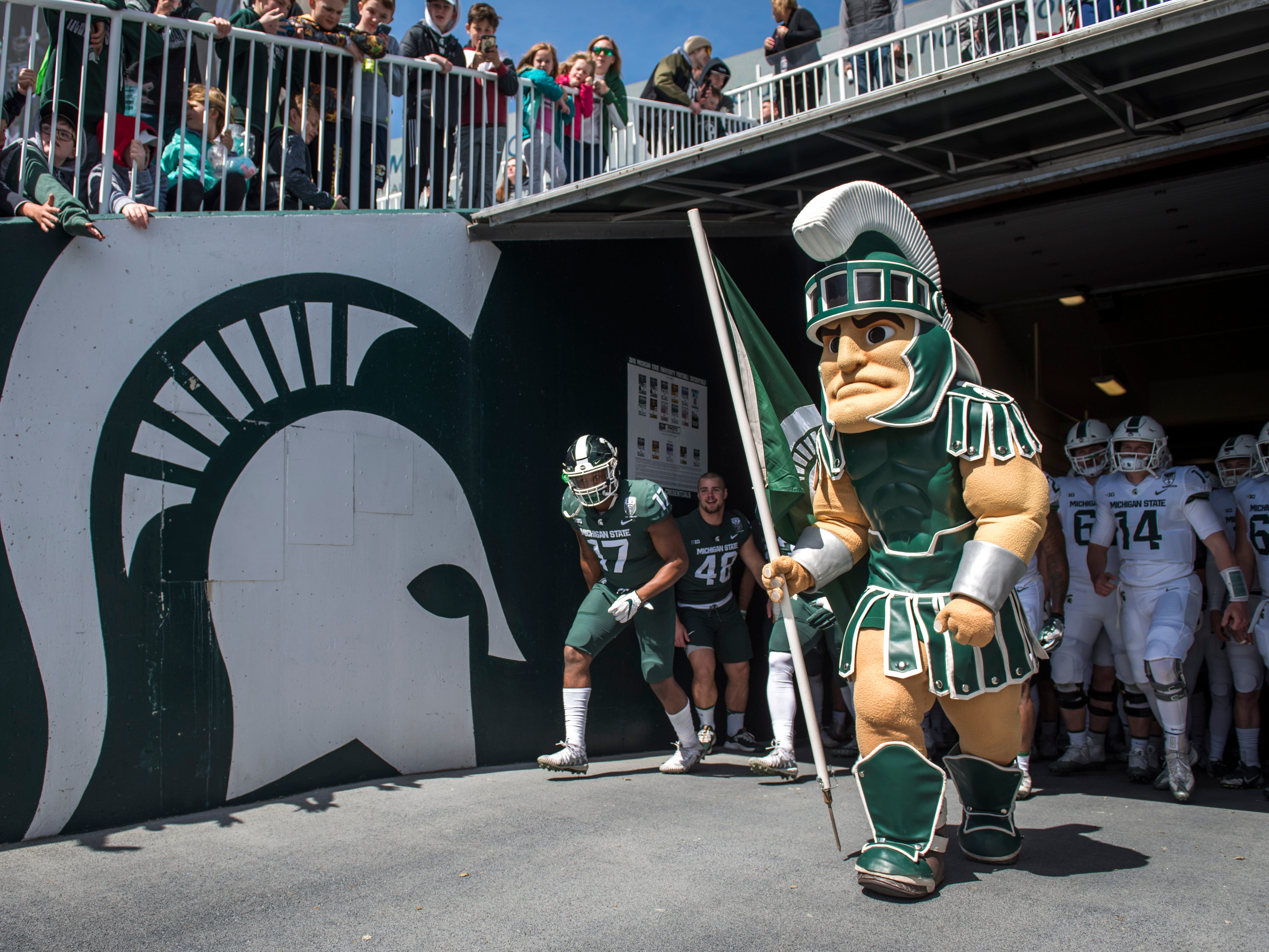 Sparty leads out the football team.