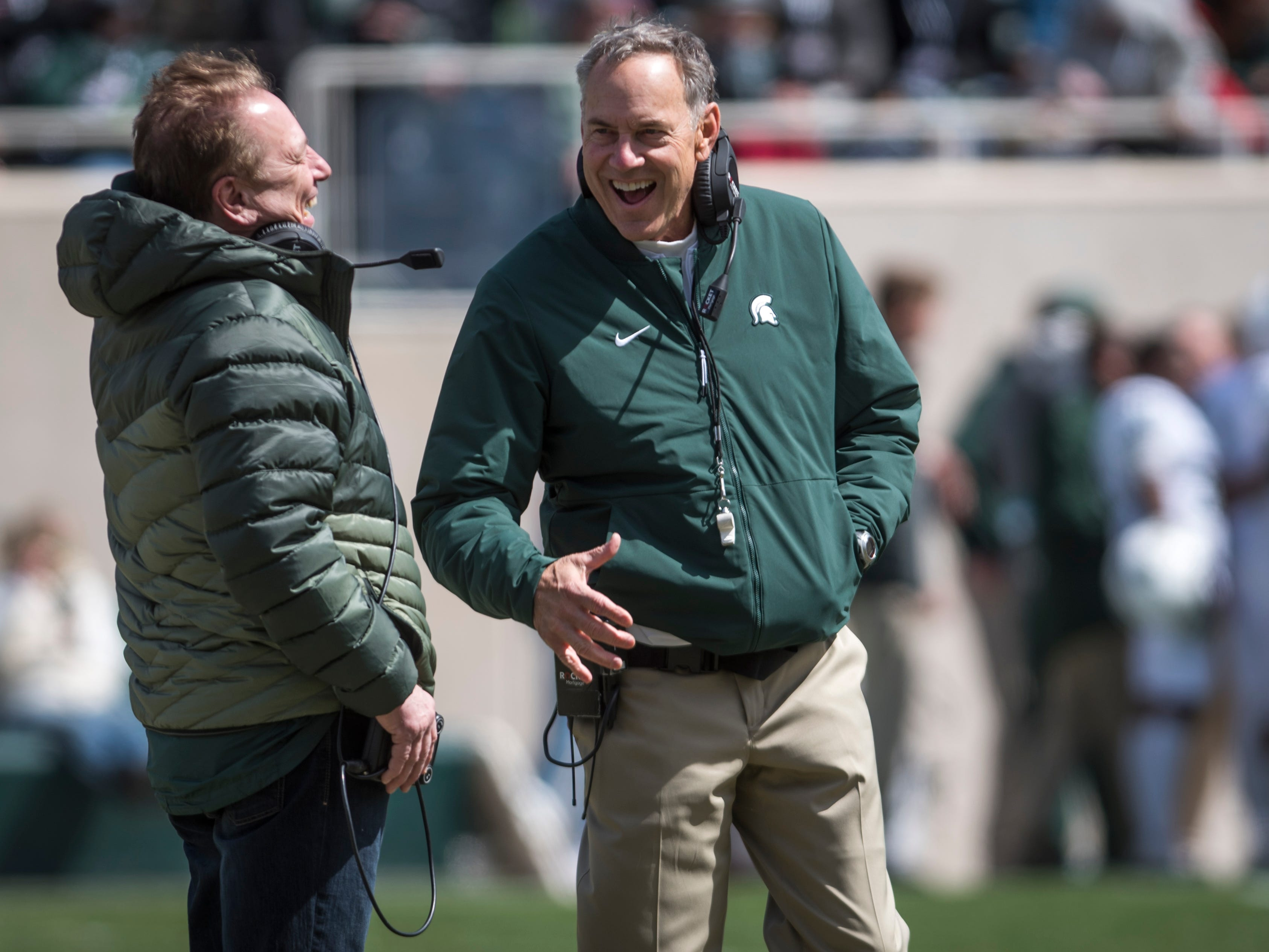 Michigan State men's basketball head coach Tom Izzo, left, jokes with football head coach Mark Dantonio.