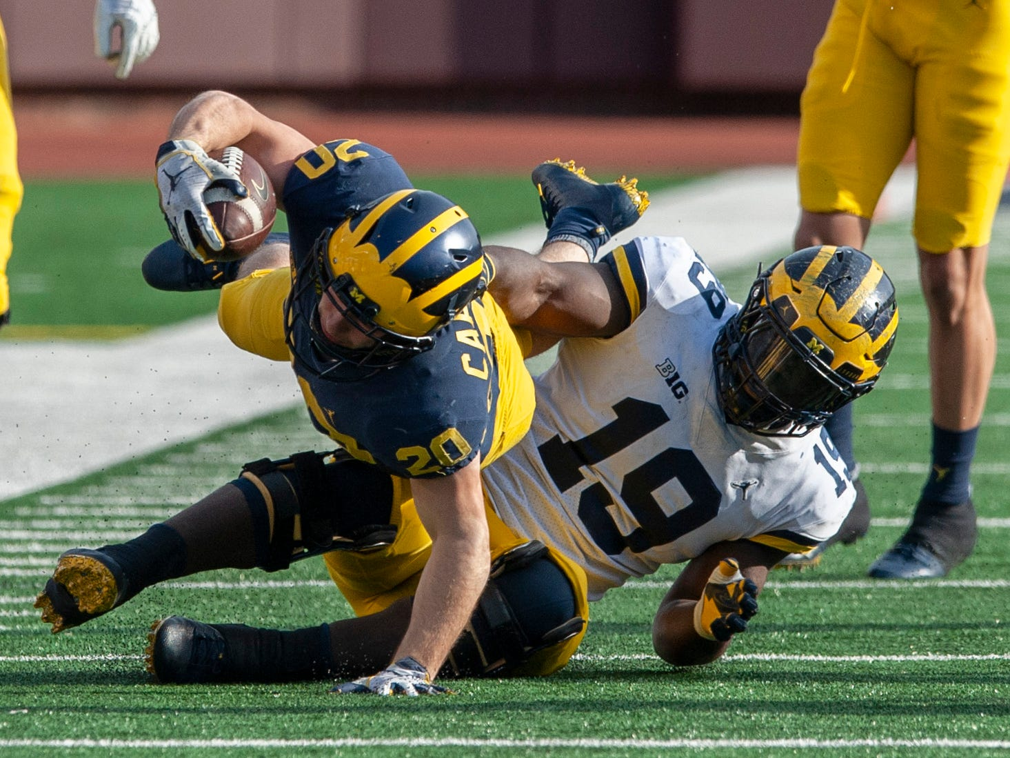 Michigan RB Nicholas Capatina stretches for extra yardage as he is taken down by DL Kwity Paye (19).