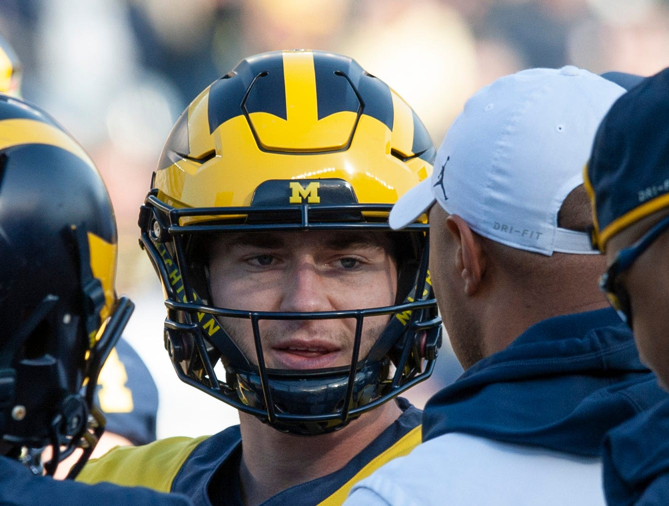 Michigan QB Shea Patterson gets some instruction from offensive coordinator Josh Gattis (white hat) during a break in the action.