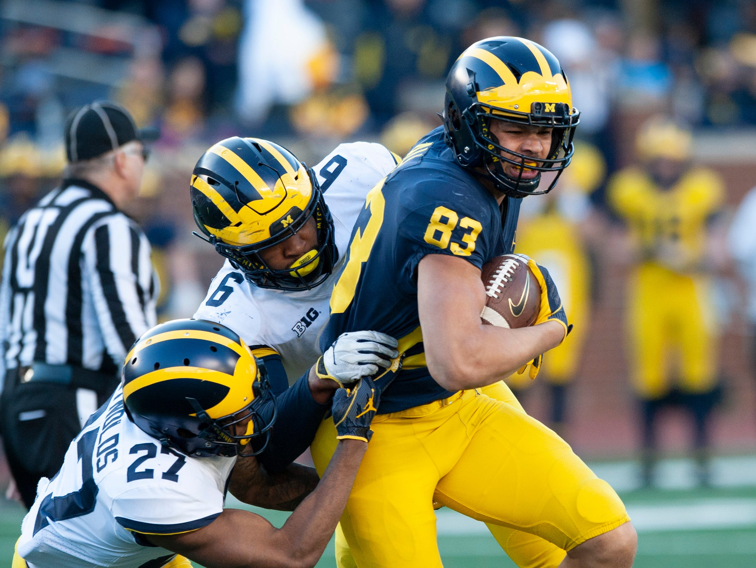 Michigan TE Erick All (83) is tackled by Michigan defenders Hunter Reynolds (27) and Michael Barrett (6) after catching a pass in the scrimmage.