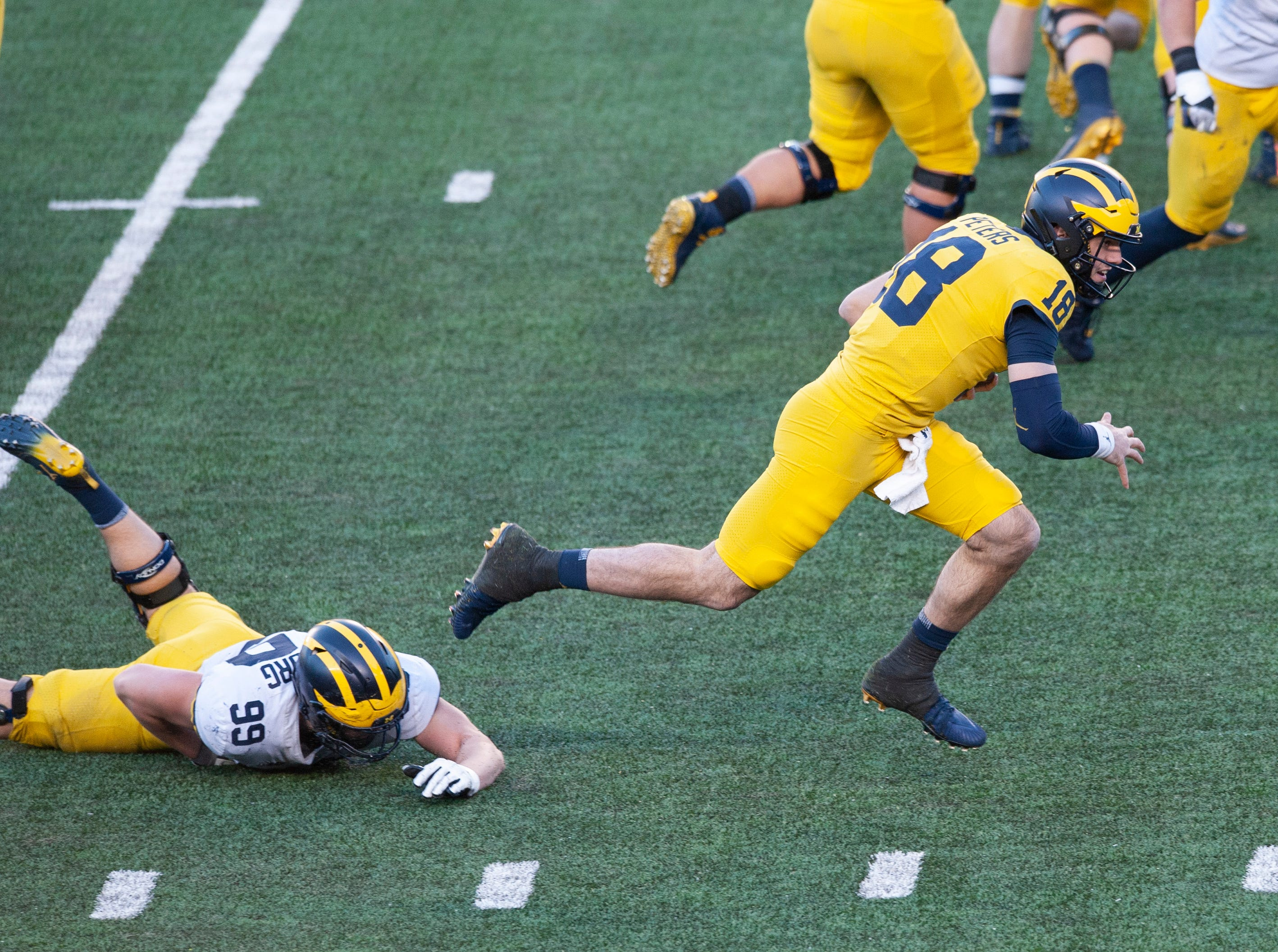 Michigan QB Brandon Peters runs away from sprawling freshman DL Gabe Newburg (99) after recovering his own fumble on the run.