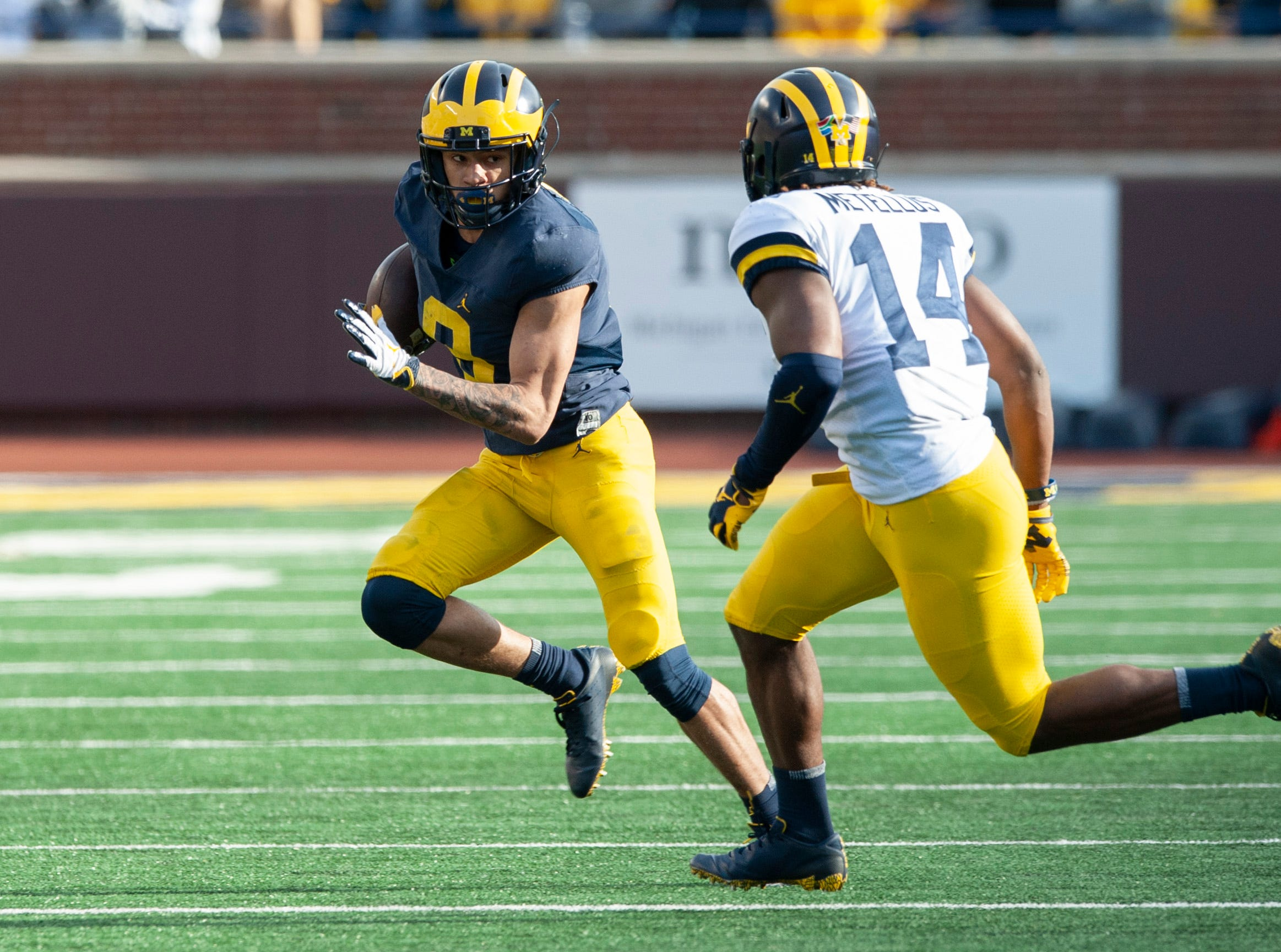 Michigan WR Ronnie Bell eludes DB Josh Metellus (14) on his way to the endzone for a touchdown.