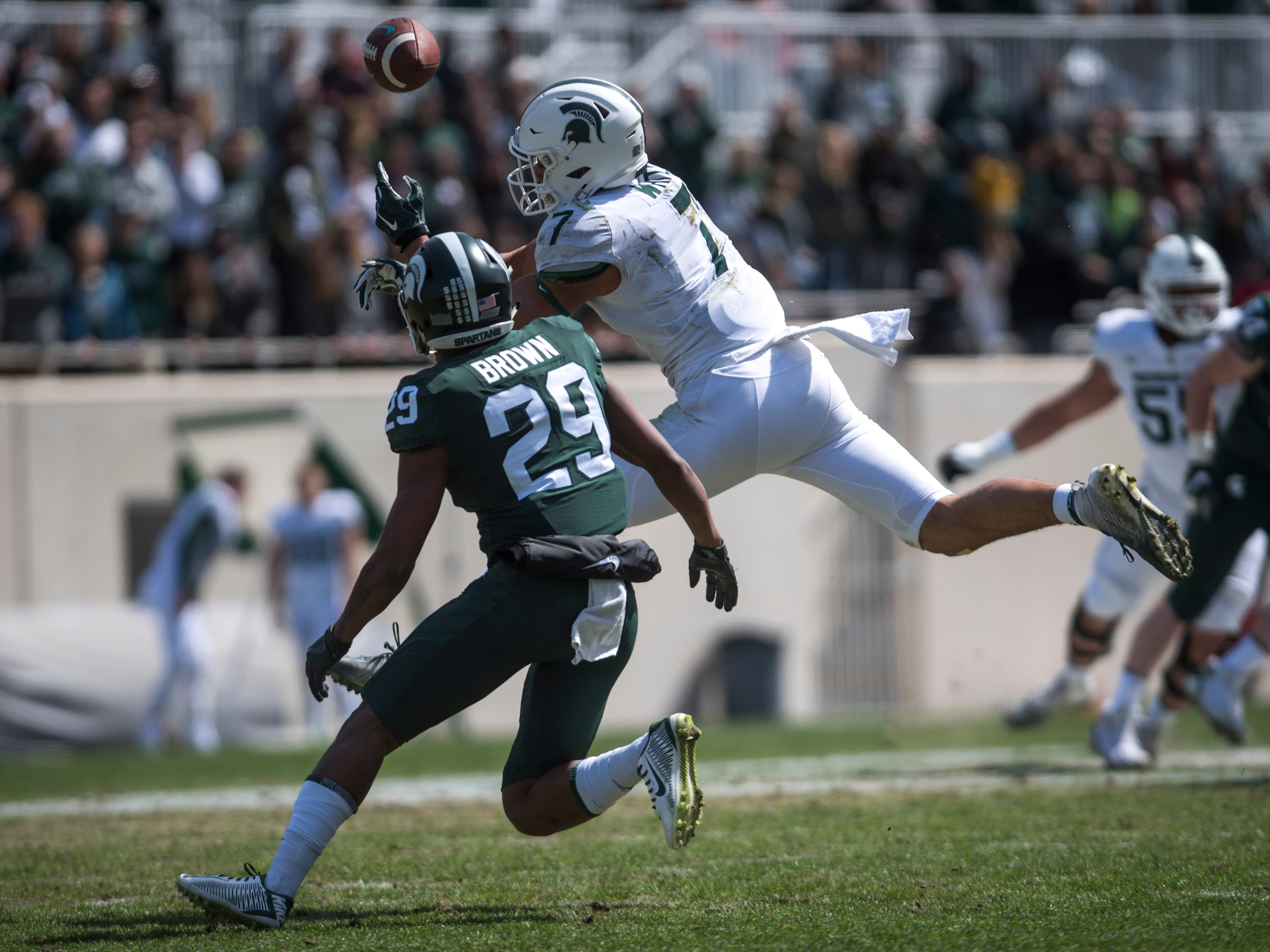 Wide receiver Cody White attempts to catch the ball while being covered by cornerback Shakur Brown.