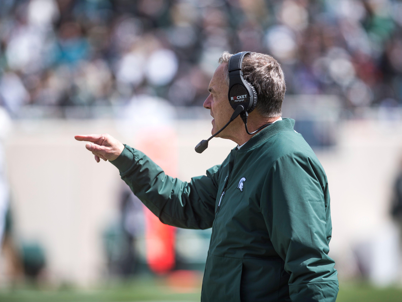 Head coach Mark Dantonio points.