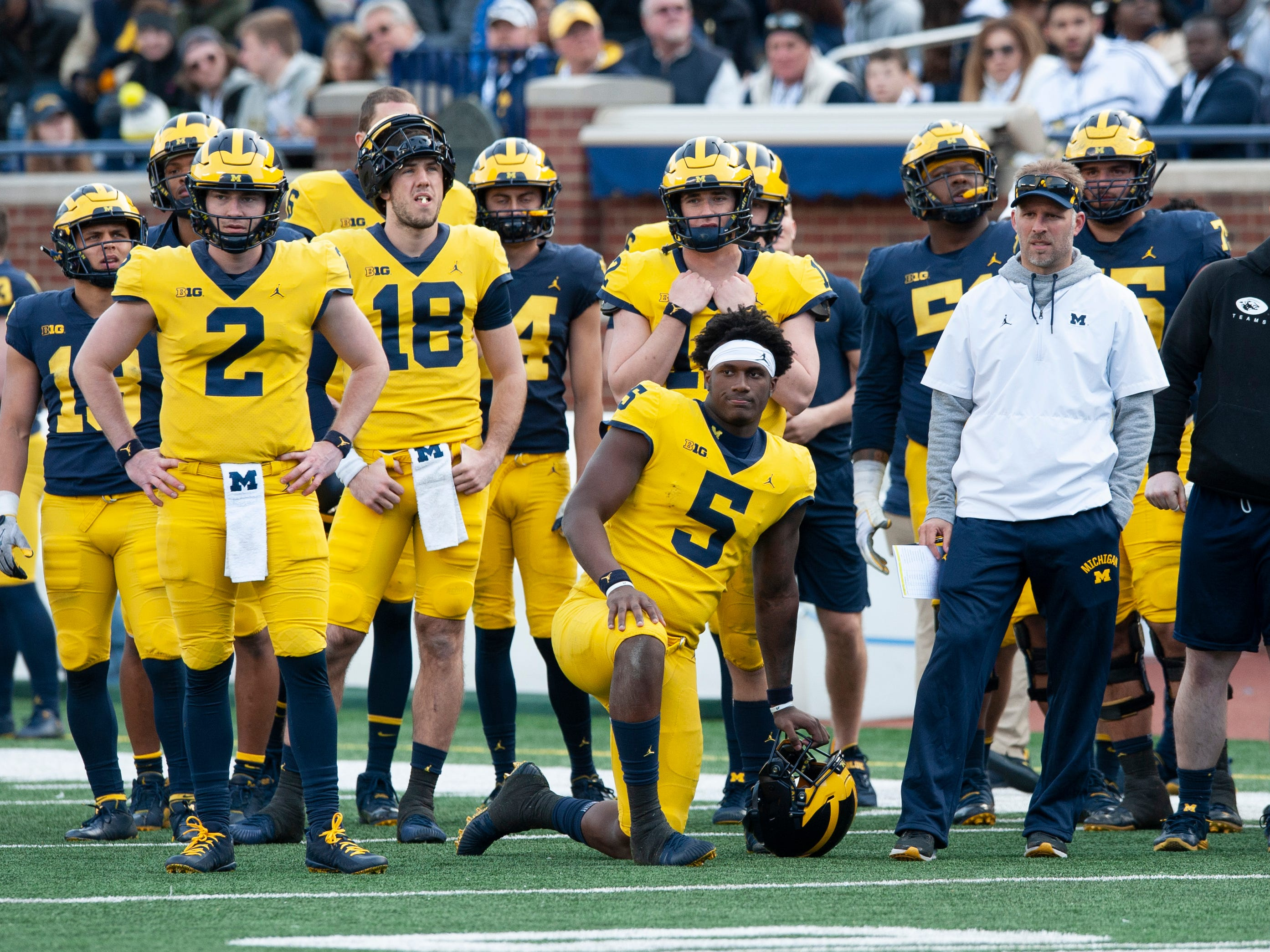 Michigan's new quarterbacks coach Ben McDaniels (right) and quarterbacks Shea Patterson (2), Brandon Peters (18), Joe Milton (5) and freshman Cade McNamara (behind Milton) watch the scrimmage from the offensive players' sideline.