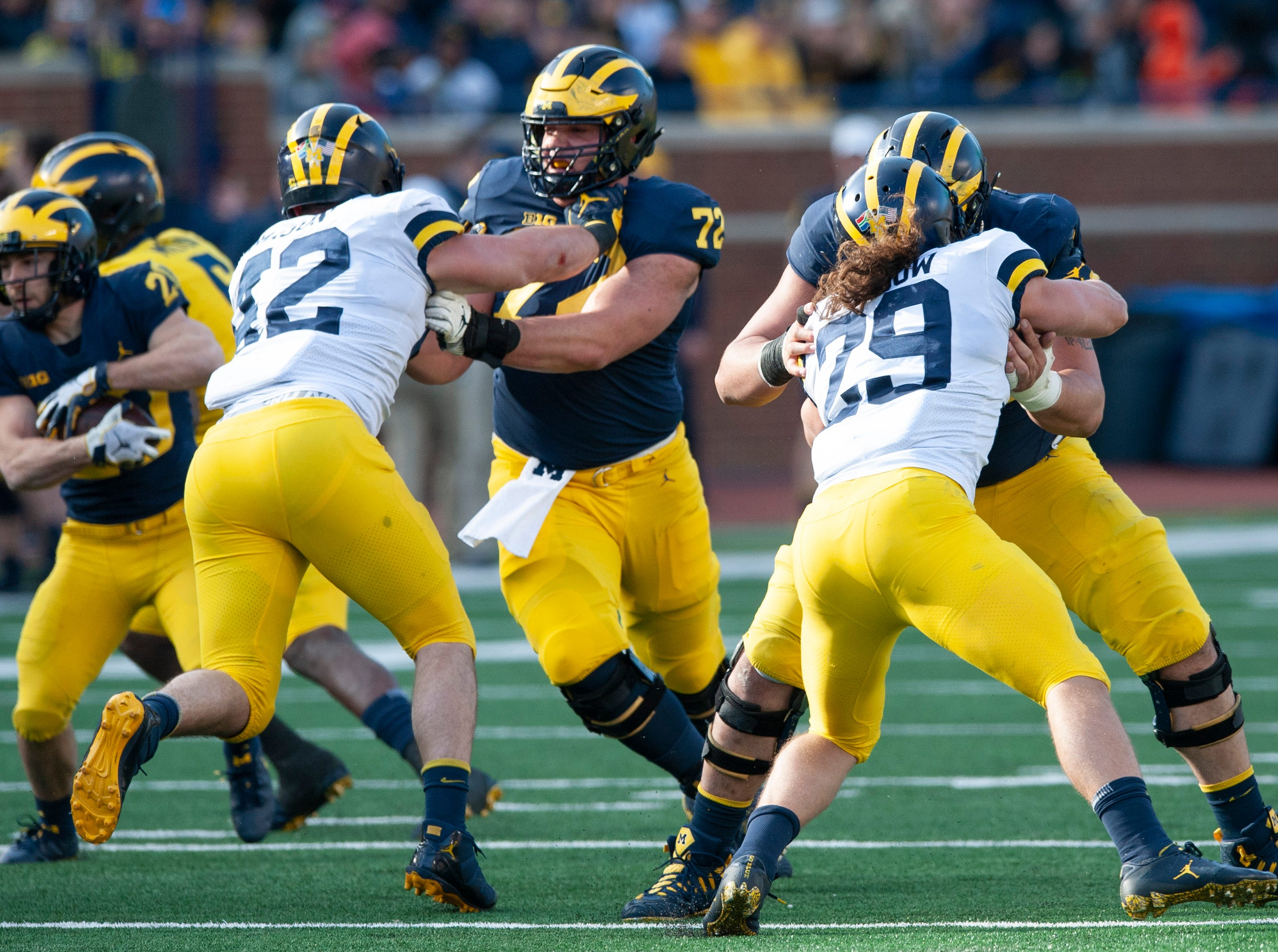 Michigan offensive lineman Stephen Spanellis holds off DL Ben Mason (42), while RB Nicholas Capatina runs the ball.