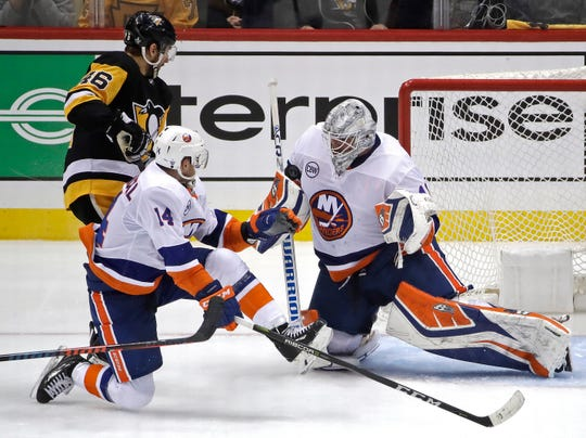 New York Islanders goaltender Robin Lehner, right, blocks a shot with Pittsburgh Penguins' Zach Aston-Reese (46) looking for the rebound with Tom Kuhnhackl (14) defending during the third period of Game 3 on Sunday.