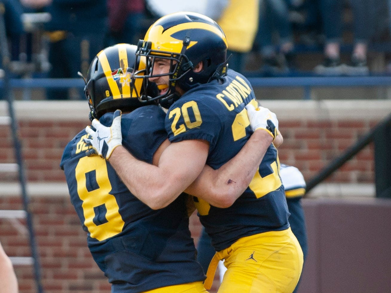 Michigan RB Nicholas Capatina gets a lift from teammate Ronnie Bell (8) after scoring a rushing touchdown.