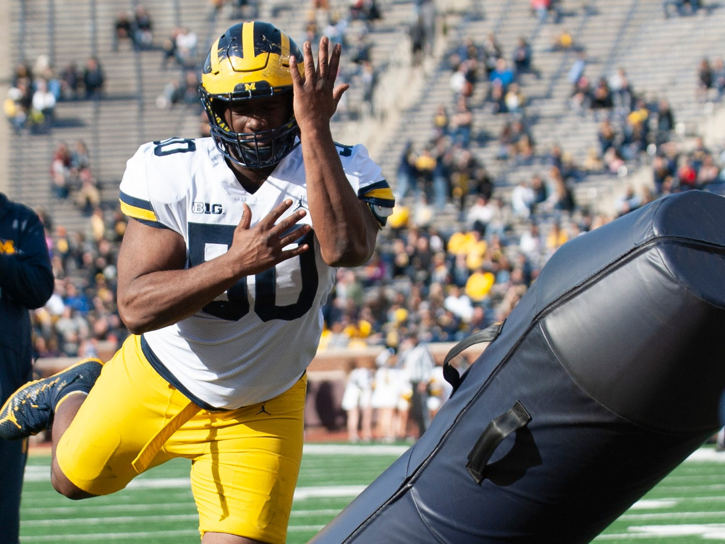 Michigan defensive lineman Michael Dwumfour knocks aside a tackling dummy during a drill.