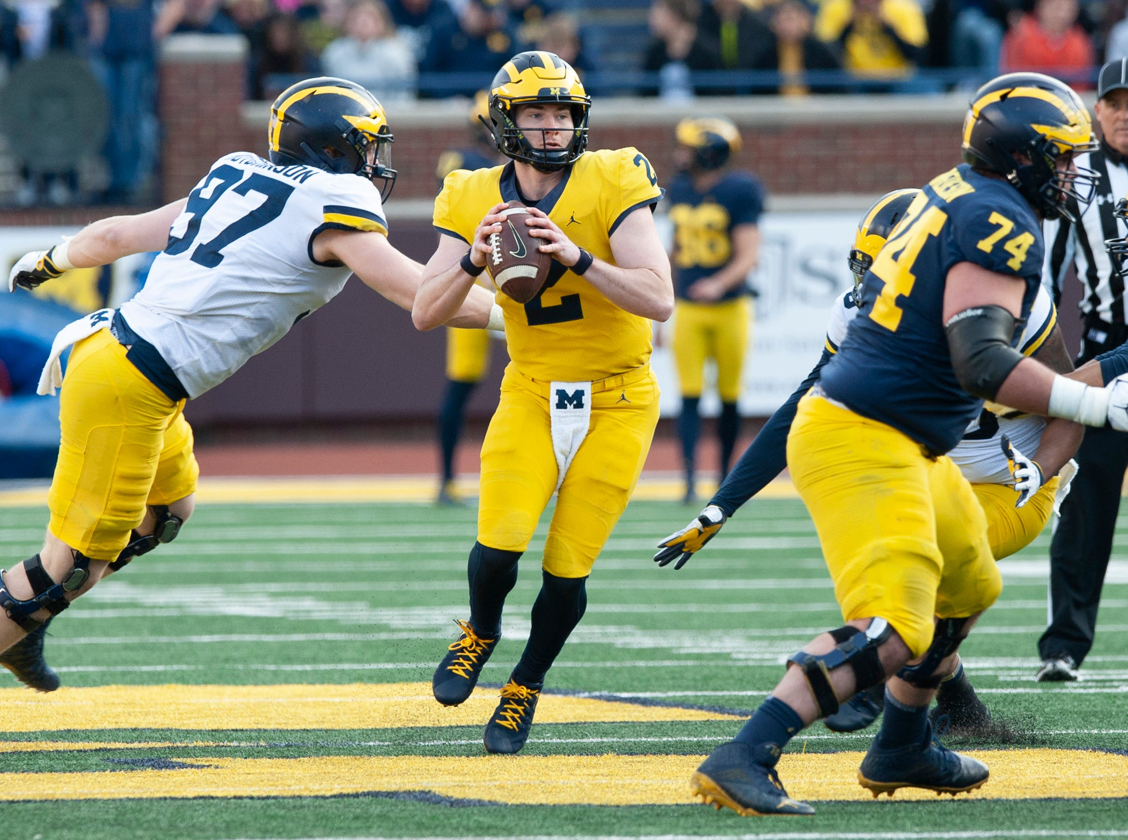 Michigan QB Shea Patterson steps up in the pocket and away from rushing DL Aidan Hutchinson (97).