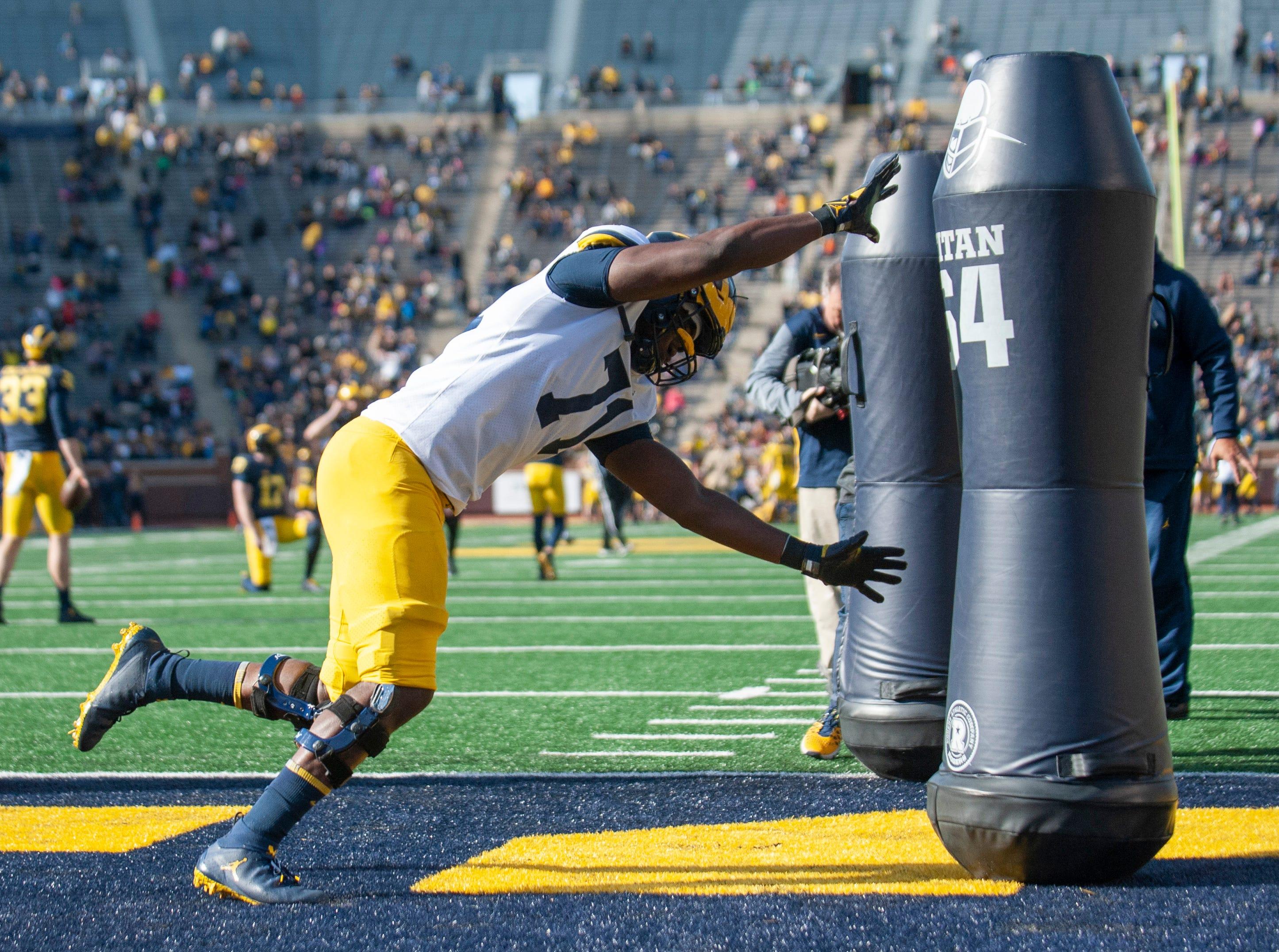 Michigan freshman defensive lineman David Ojabo attacks a series of tackling dummies during a drill.