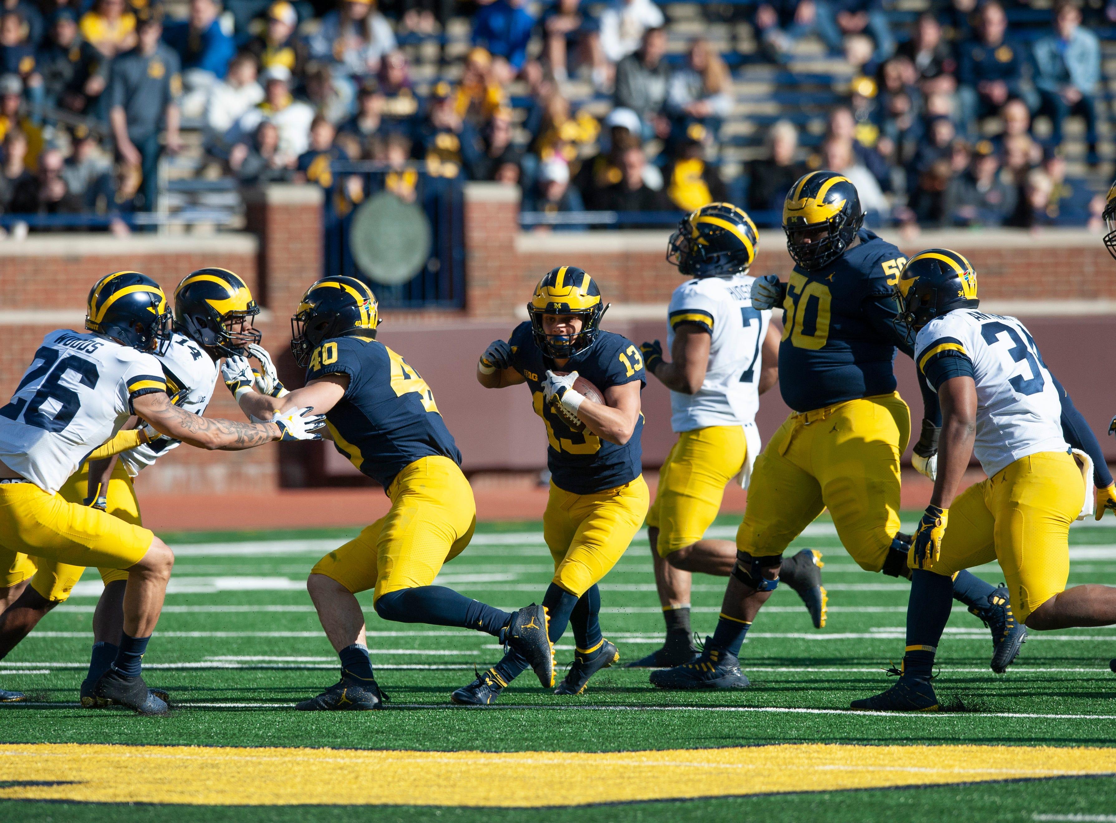 Michigan running back Tru Wilson (13) finds a seam in the Michigan defense.