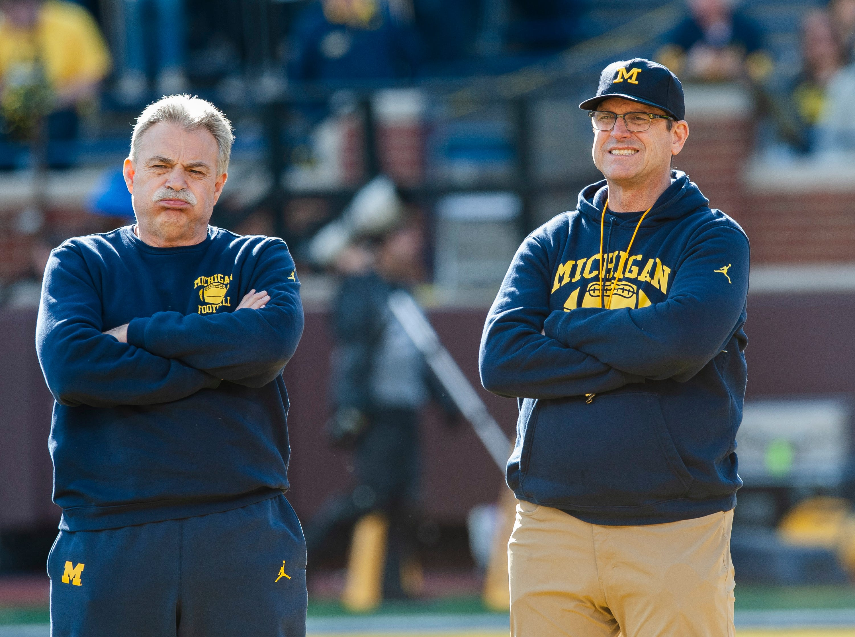 Michigan defensive coordinator Don Brown and head coach Jim Harbaugh look less than enthusiastic as they watch the players run through drills before the start of the scrimmage known as the 2019 Michigan Spring Game at Michigan Stadium in Ann Arbor on Saturday, April 13, 2019.