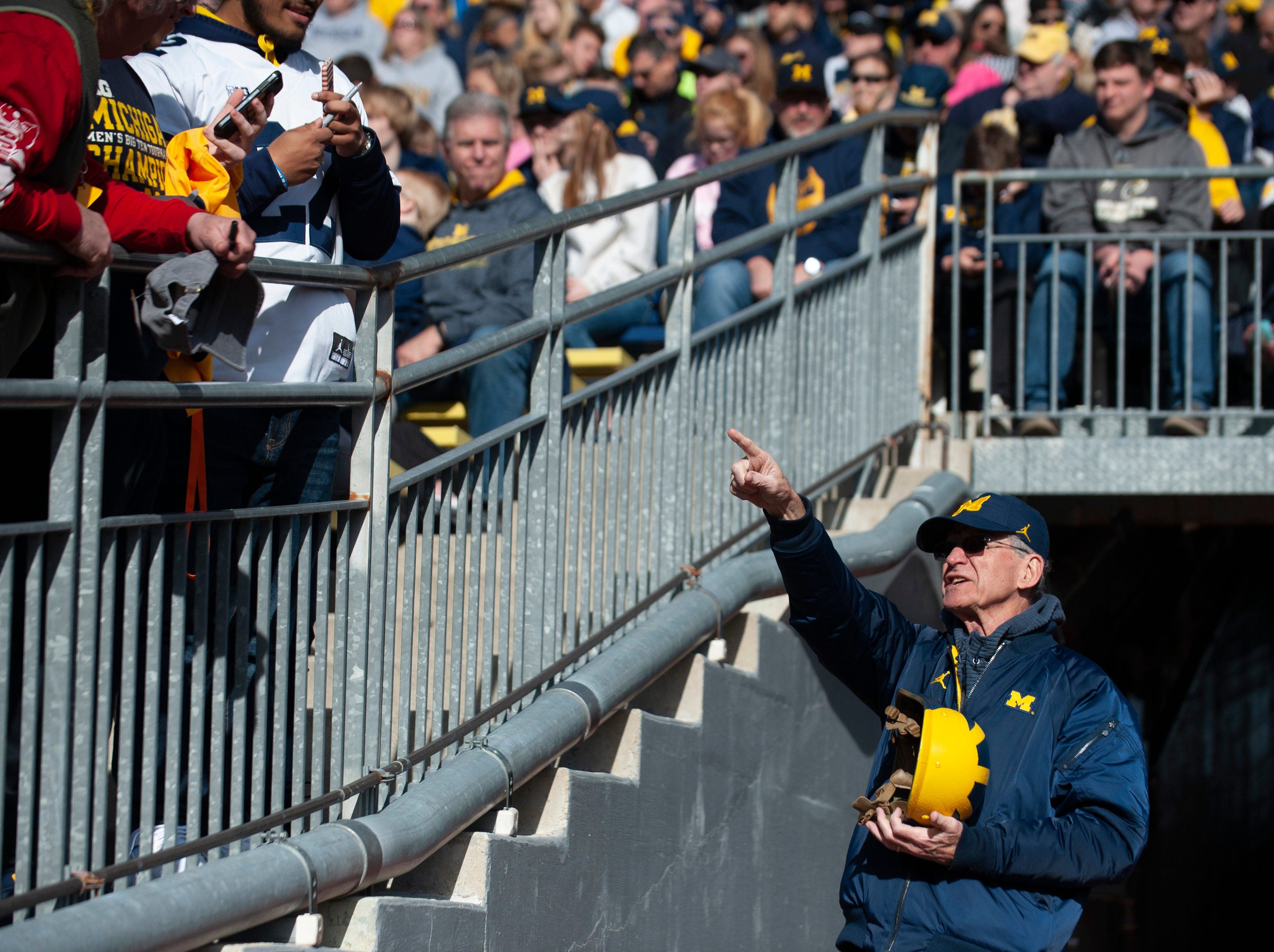 Jack Harbaugh, father of Michigan head coach Jim Harbaugh, points to fans at the entrance to the Michigan Stadium tunnel.