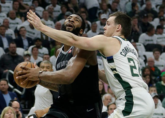 Pistons center Andre Drummond, left, drives to the basket against the Bucks' Pat Connaughton during the first half Sunday in Milwaukee
