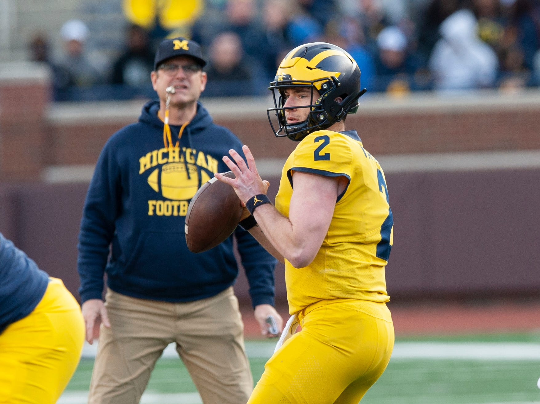 Michigan QB Shea Patterson looks for an open receiver with head coach Jim Harbaugh looking on during the scrimmage.