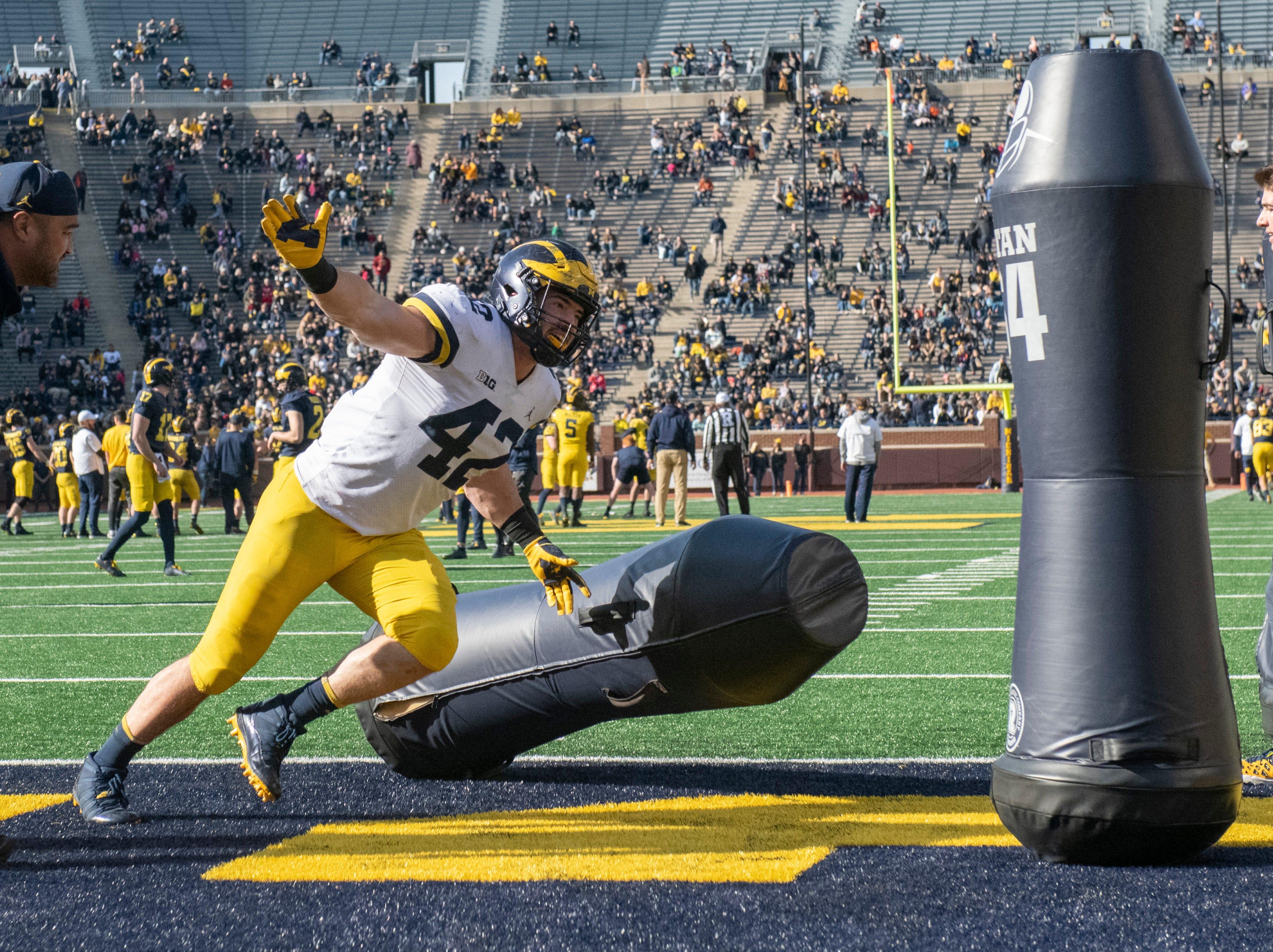 Michigan defensive lineman Ben Mason knocks down tackling dummies during a drill.