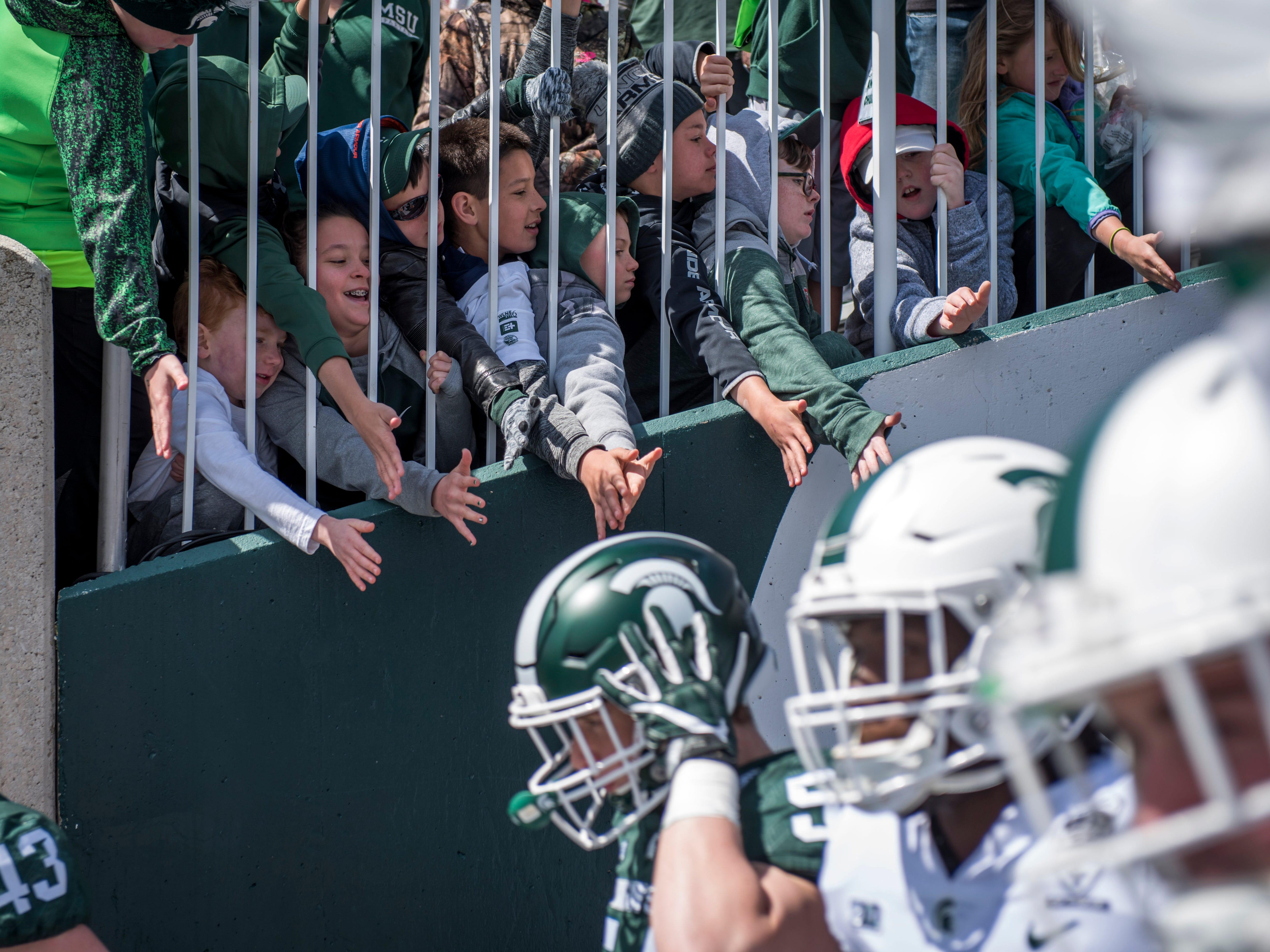 Michigan State fans hold their hands out for high fives.