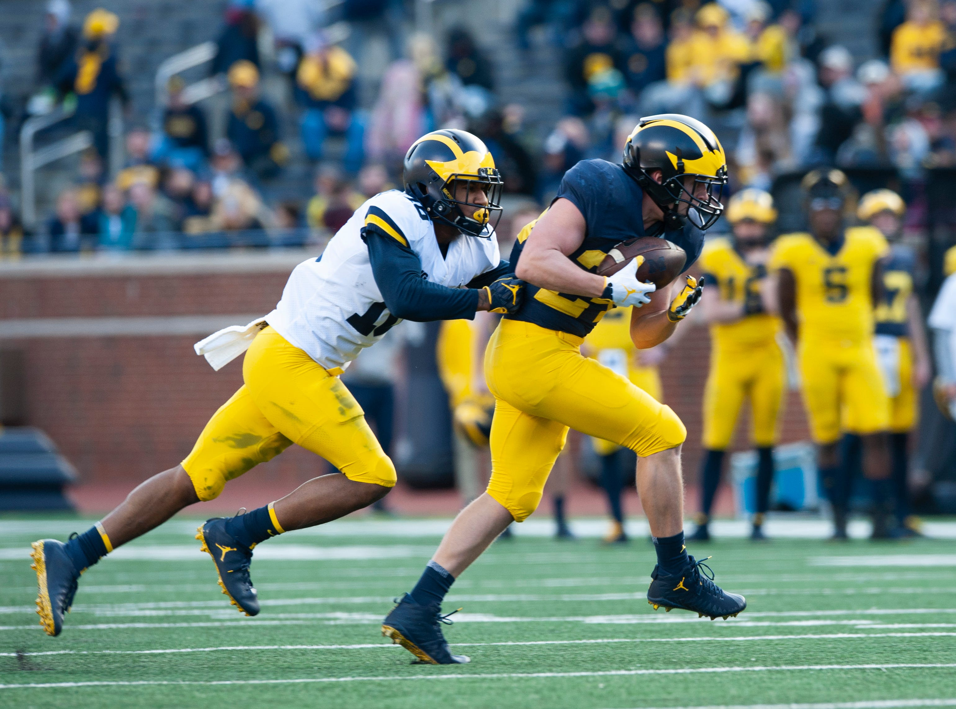Michigan WR Jake Martin picks up some extra yardage after catching a pass before being tackled by Jalen Kelly-Powell (16).