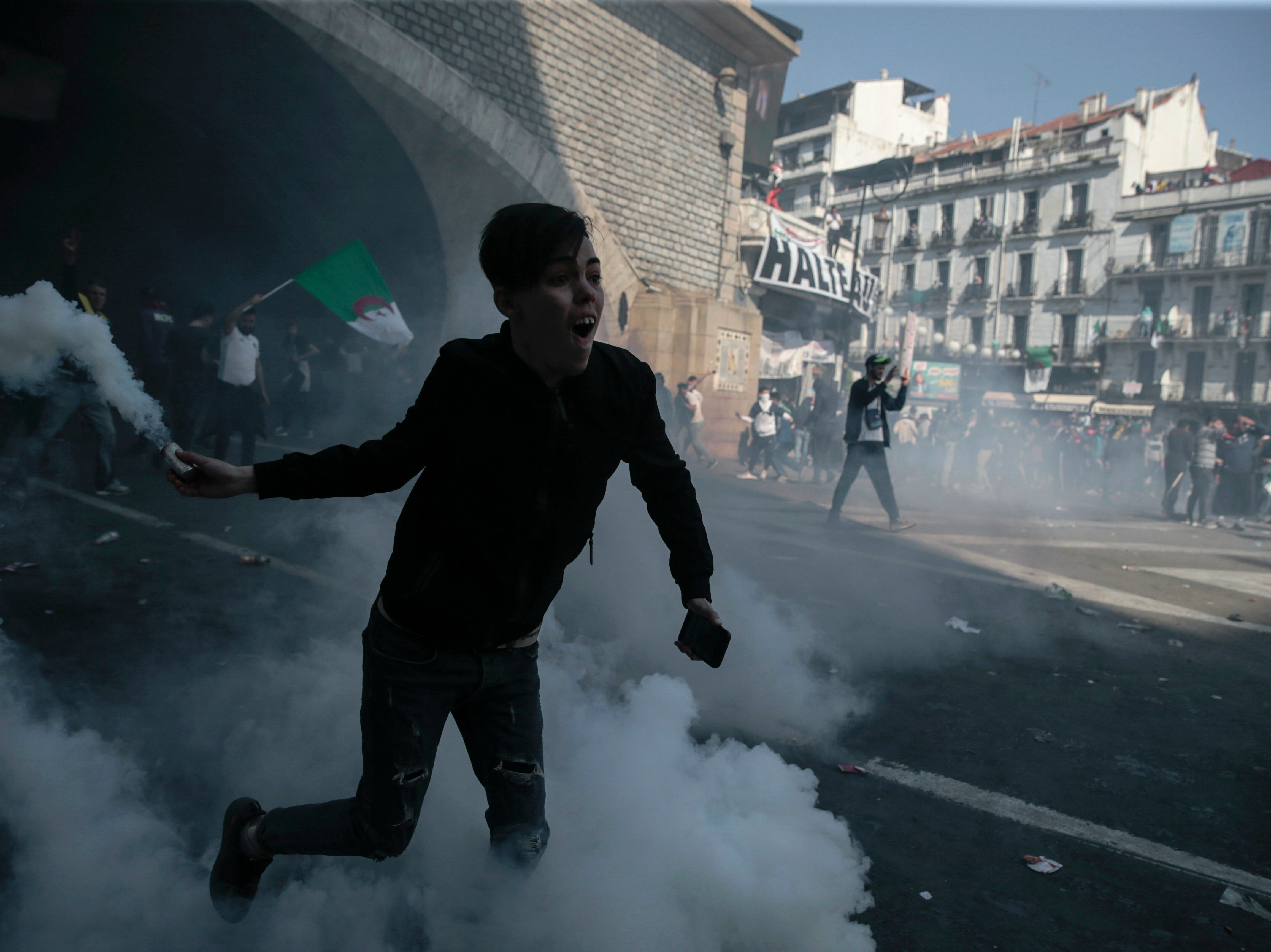 Protesters clash with police officers during a demonstration against the country's leadership, in Algiers, Friday, April 12, 2019. Heavy police deployment and repeated volleys of water cannon and tear gas didn't deter masses of Algerians from packing the streets of the capital Friday, insisting that their revolution isn't over just because the president stepped down.