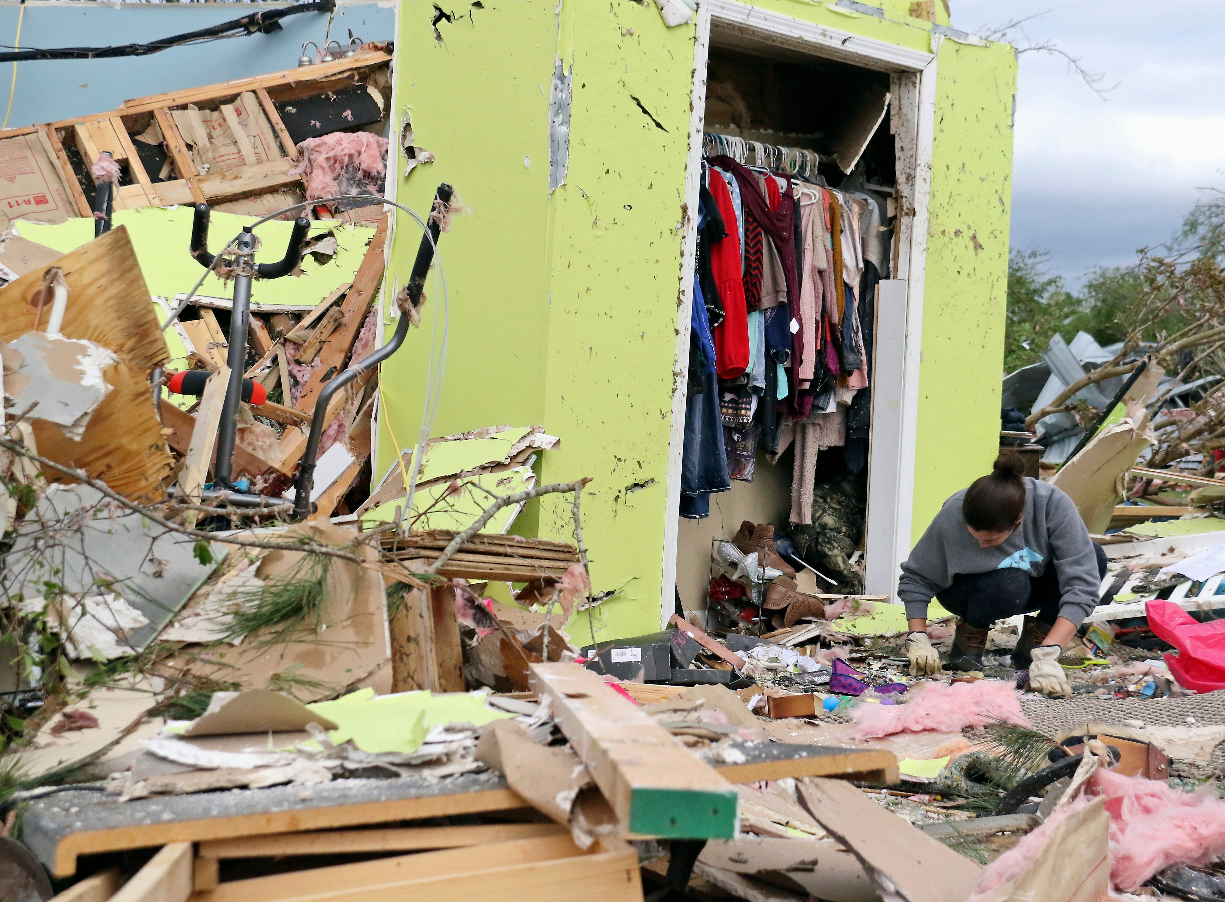 Leslie Harrington kneels down to help a former neighbor and family friend look for jewelry in her destroyed home along Seely Drive outside of Hamilton, Miss., after a deadly storm moved through the area on Sunday, April 14, 2019.