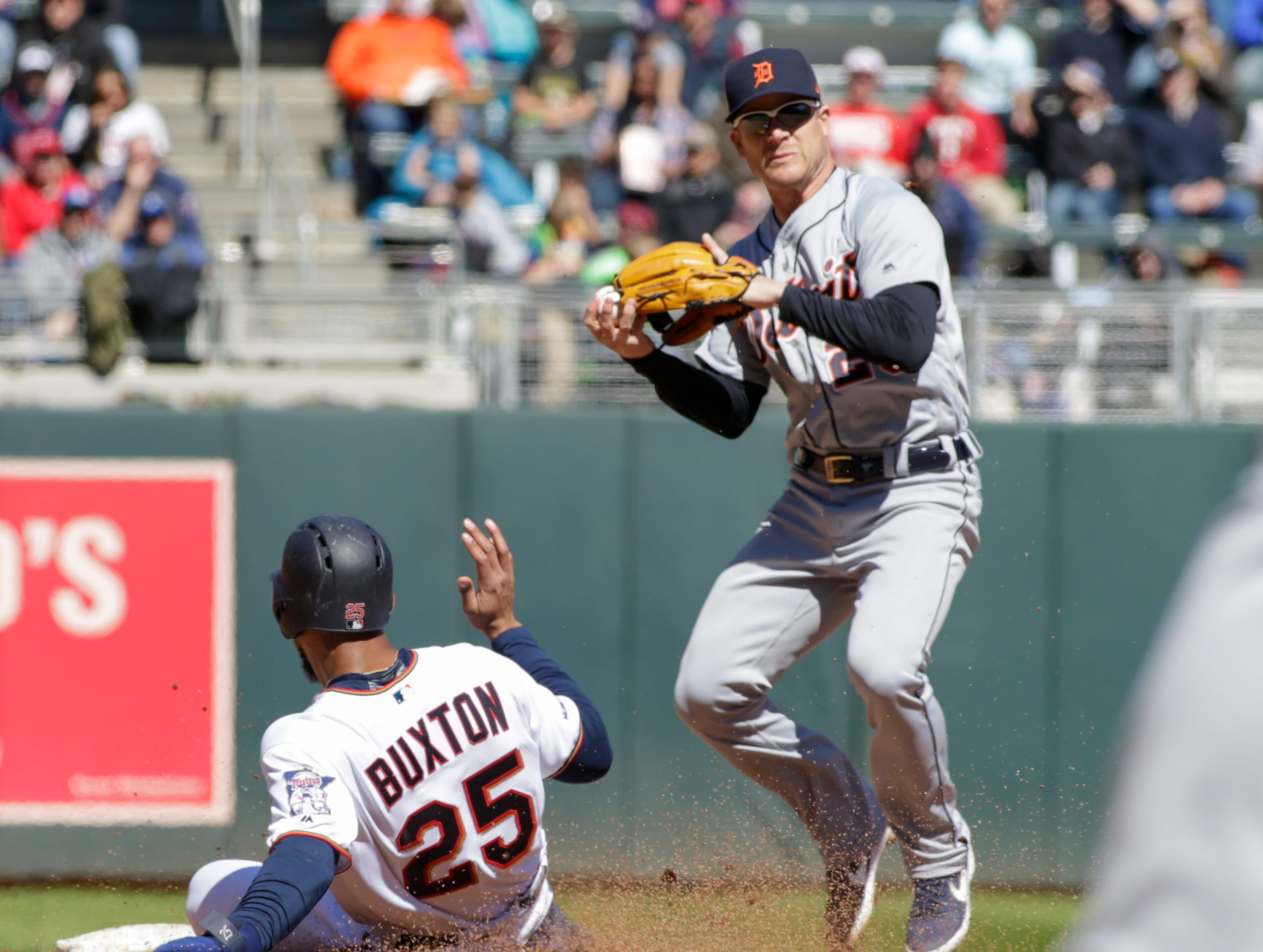 Minnesota Twins' Byron Buxton (25) is forced on the first half of a double-play by Detroit Tigers shortstop Gordon Beckham (29) during the fourth inning.
