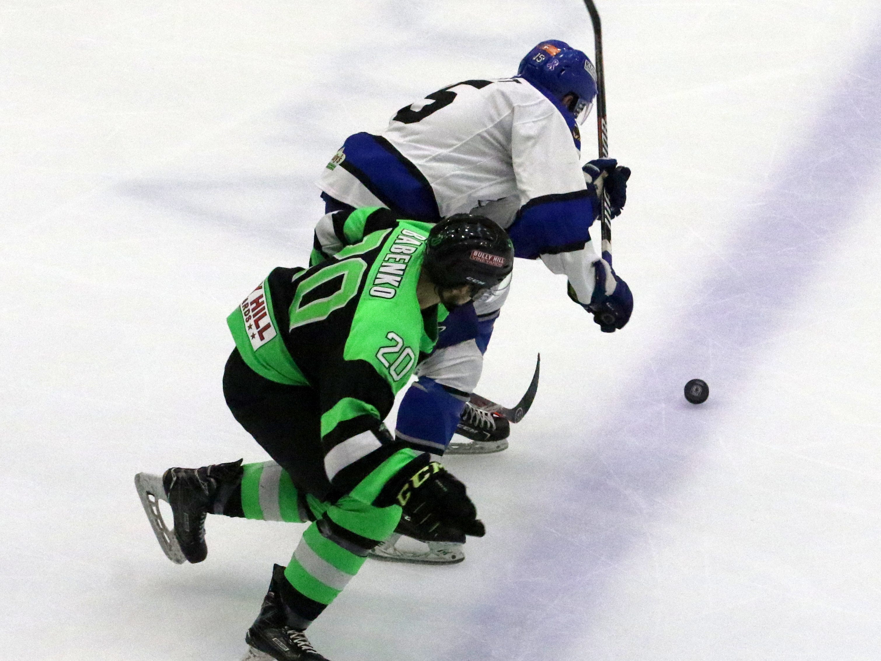 Watertown's Cameron Dimmitt (top) and Elmira's Dmytro Babenko chase the puck during Game 2 of the Federal Hockey League semifinal series between the Enforcers and Wolves on April 13, 2019 at Elmira's First Arena.