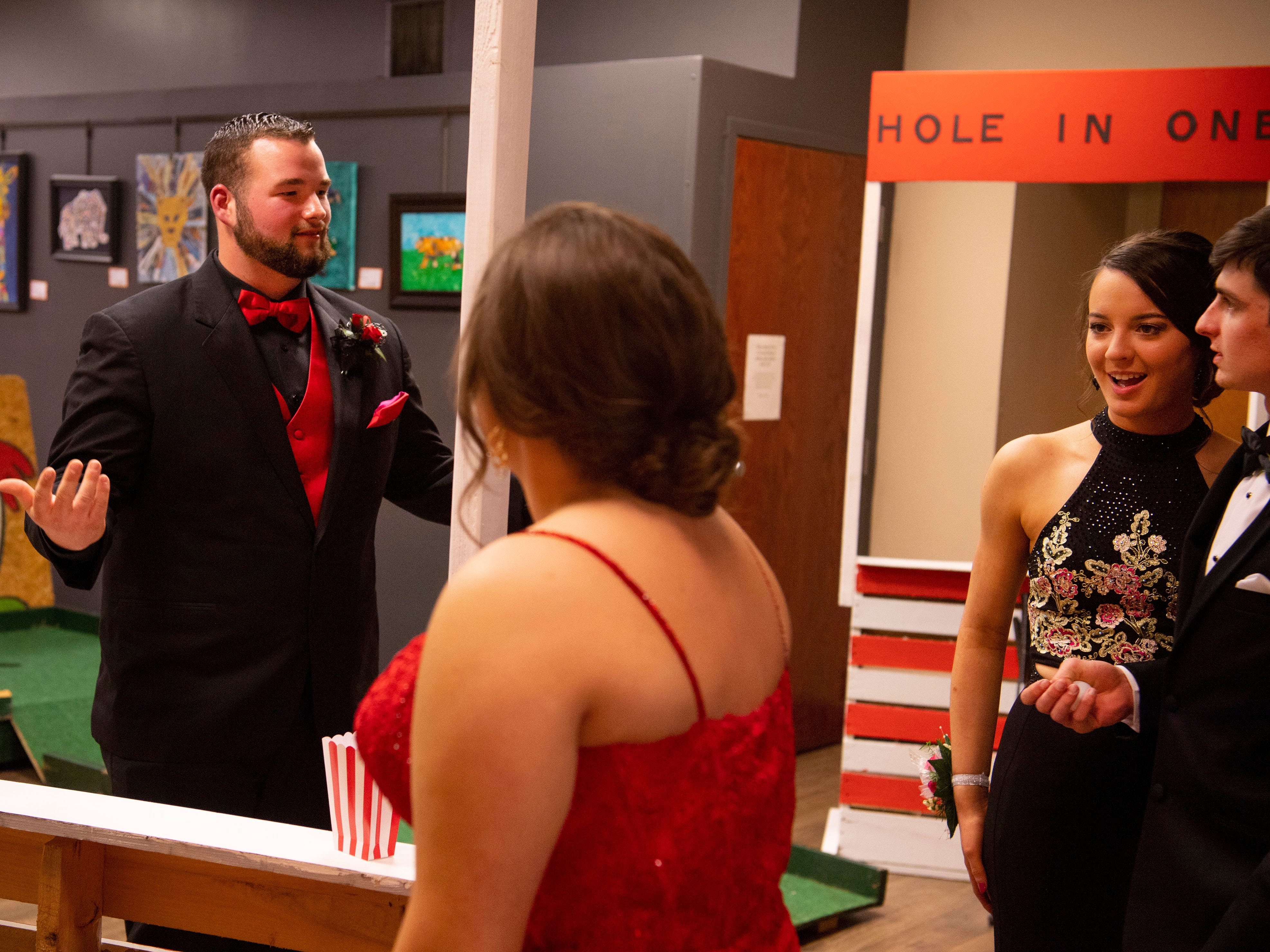 """Wyatt Wood, 17, left, celebrates his 3-for-3 showing in the Ping Pong Toss at """"The Greatest Prom on Earth"""" at Milestones Saturday night. Also pictured are, from left, his date, Keily Burton, 17, Payton Bailey, 18, and Blake Dillon, 17."""