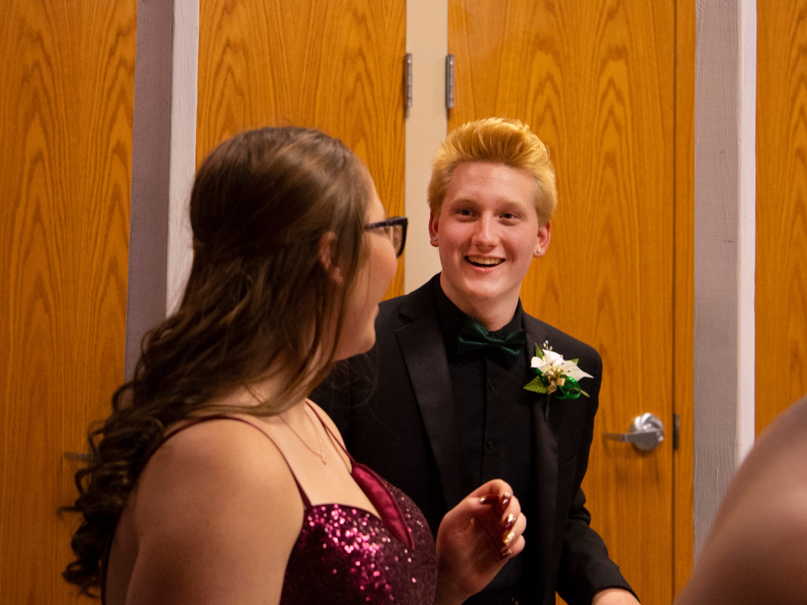 """Harrison junior Jeremiah Angel, 17, takes his place behind the Ping Pong Toss at """"The Greatest Prom on Earth"""" at Milestones Saturday night."""