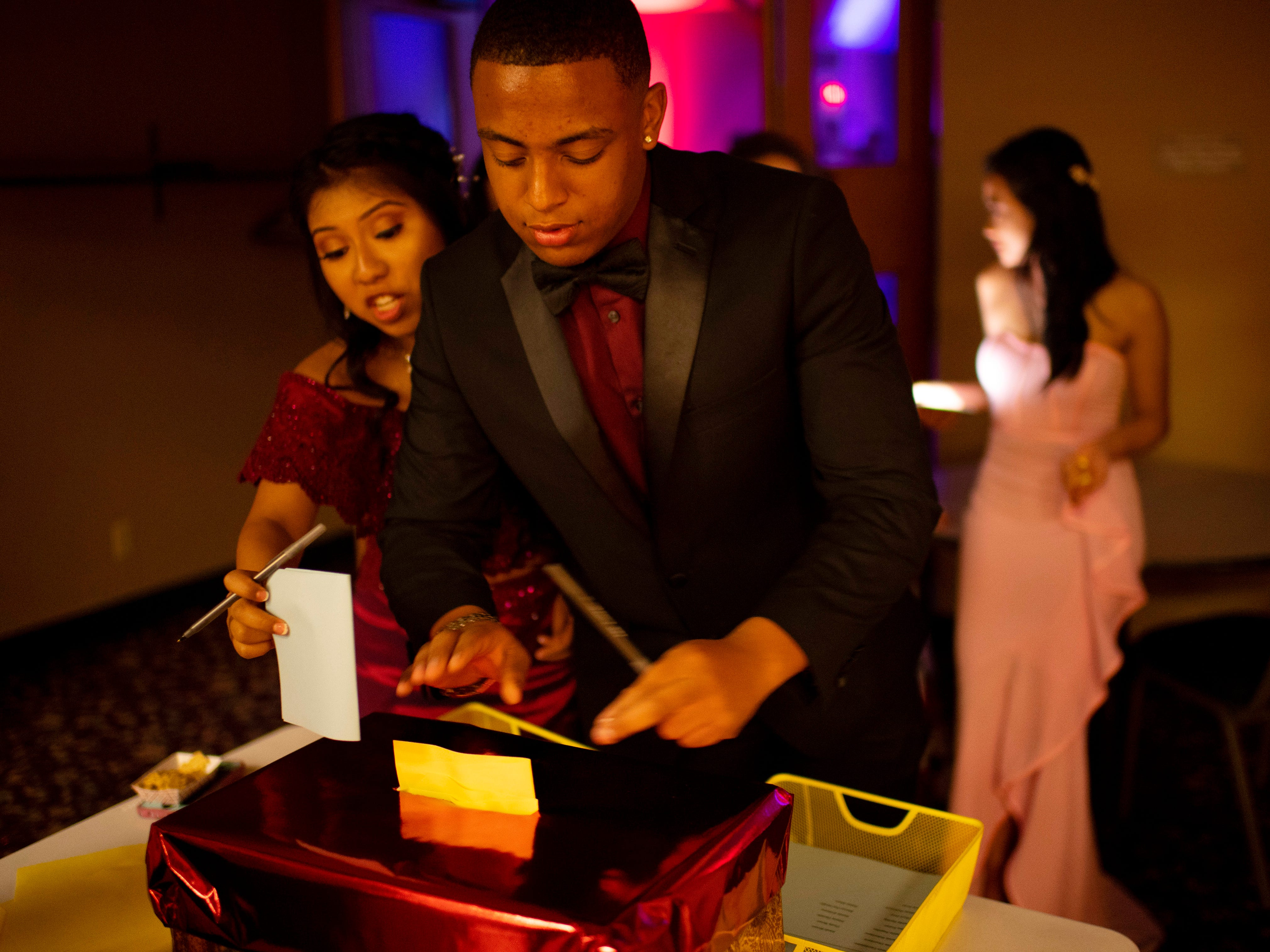 """Harrison students Julissa Coronel, 18, left, and Braxxton Murray, 17, cast their ballots for the homecoming court at """"The Greatest Prom on Earth"""" at Milestones Saturday night."""