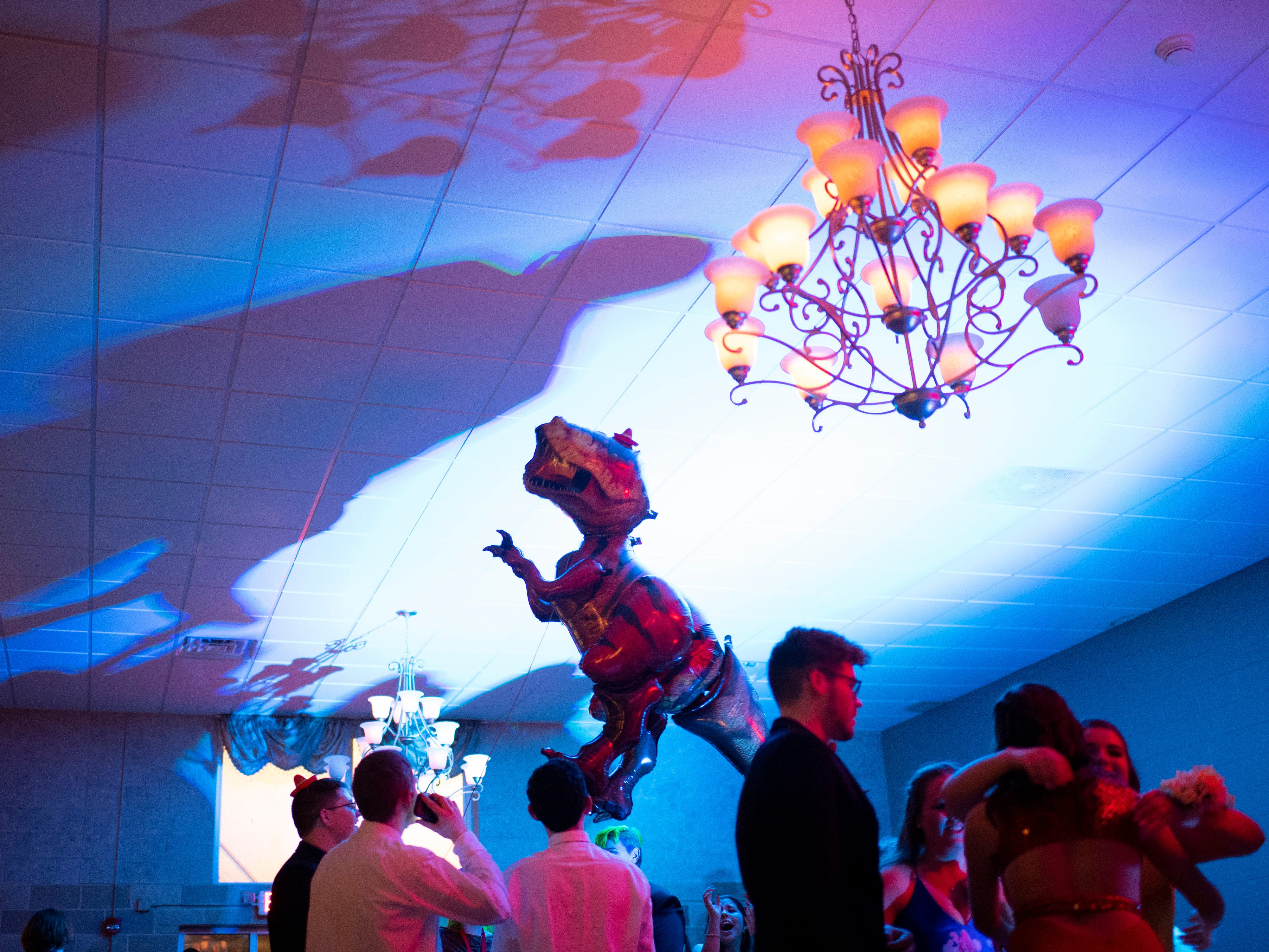 """An inflatable T-rex floats above the dance floor with the help of the Signature School's """"Jurassic Prom"""" attendees at Party Central Saturday night."""