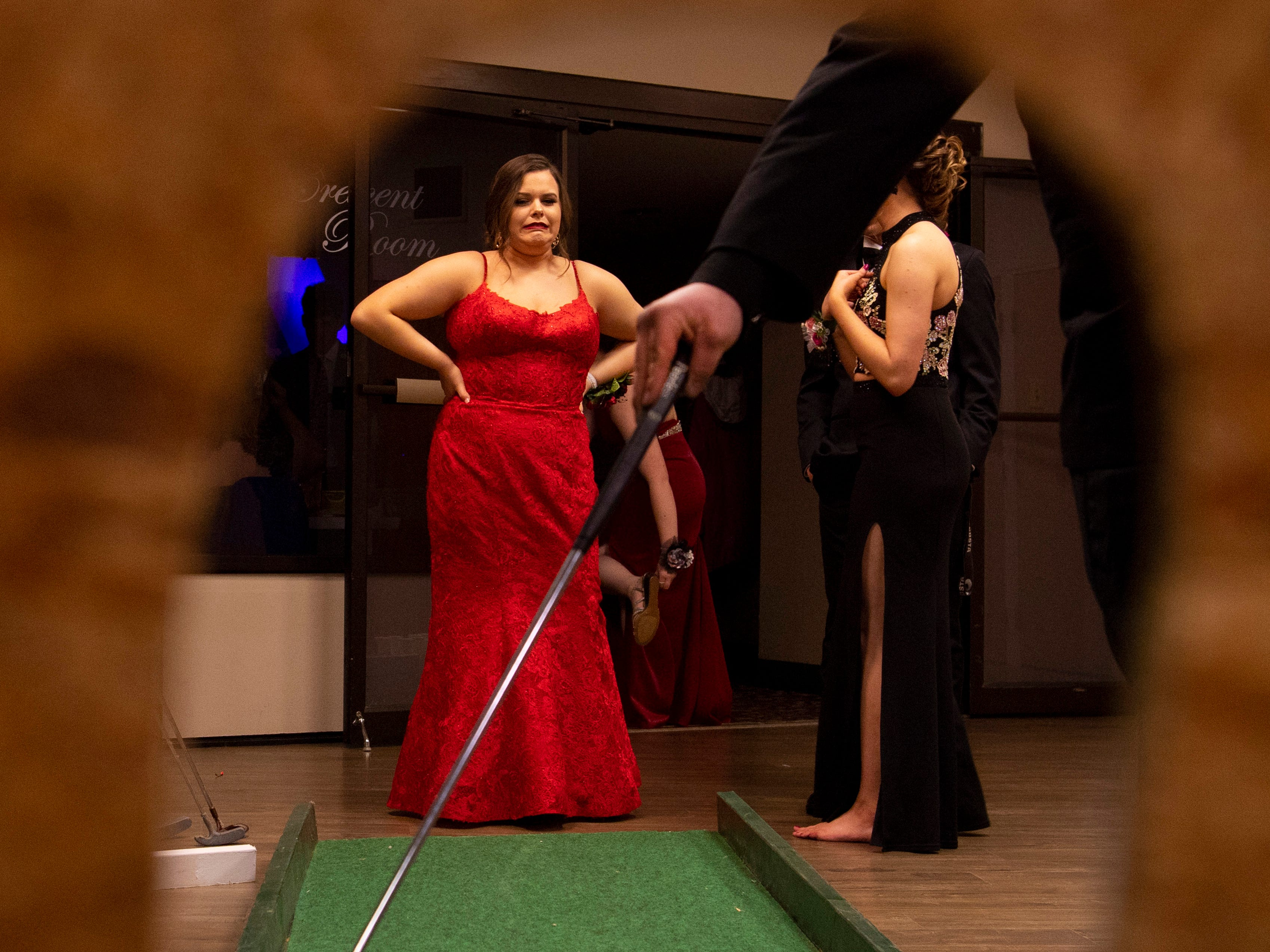 """Keily Burton, 17, reacts to her date, Wyatt Wood's, golf putt at the Hole in One game at """"The Greatest Prom on Earth"""" at Milestones Saturday night."""