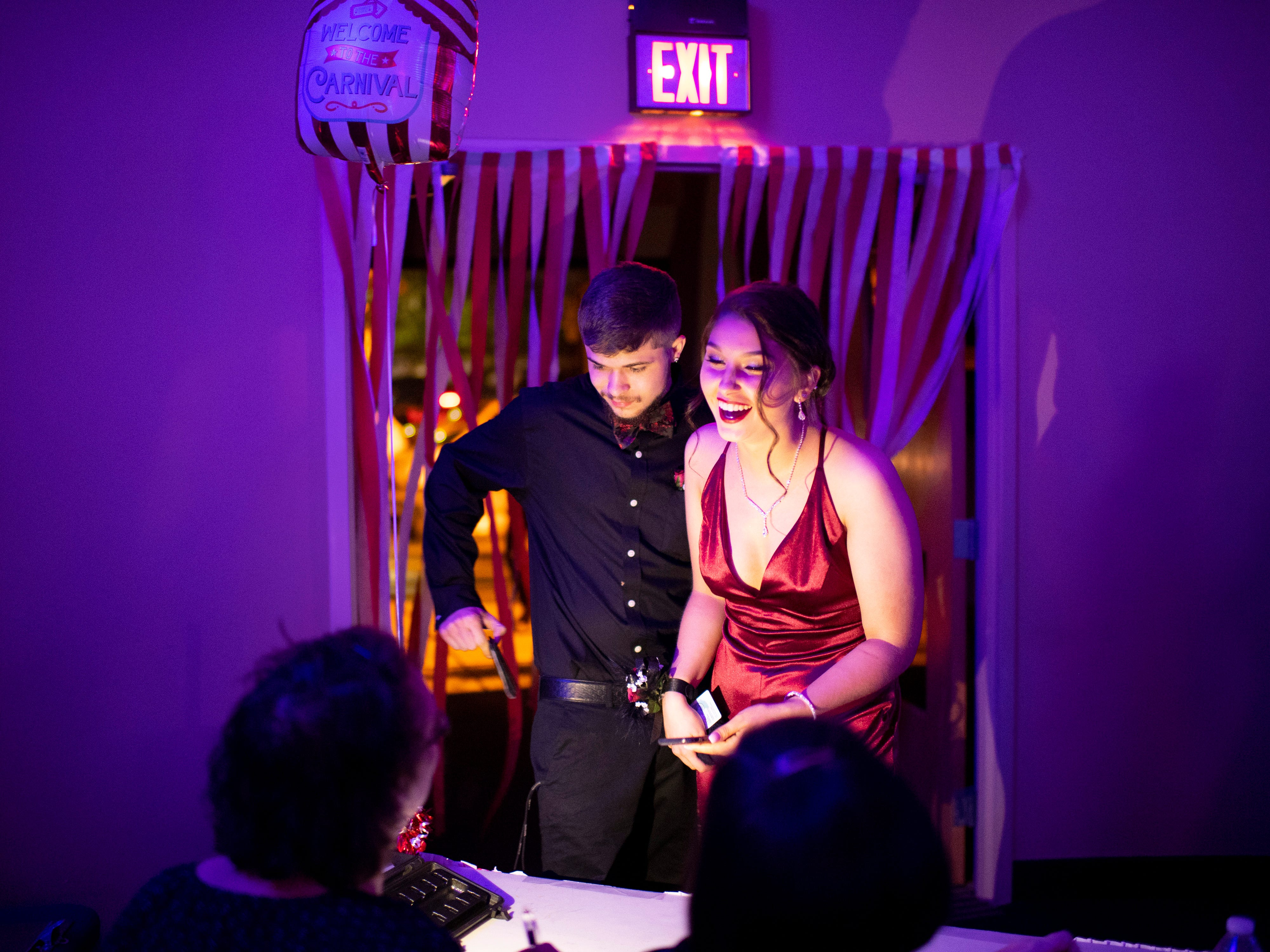 """Harrison seniors Cassidy Shafer and Sebastian White check in to """"The Greatest Prom on Earth"""" at Milestones Saturday night."""