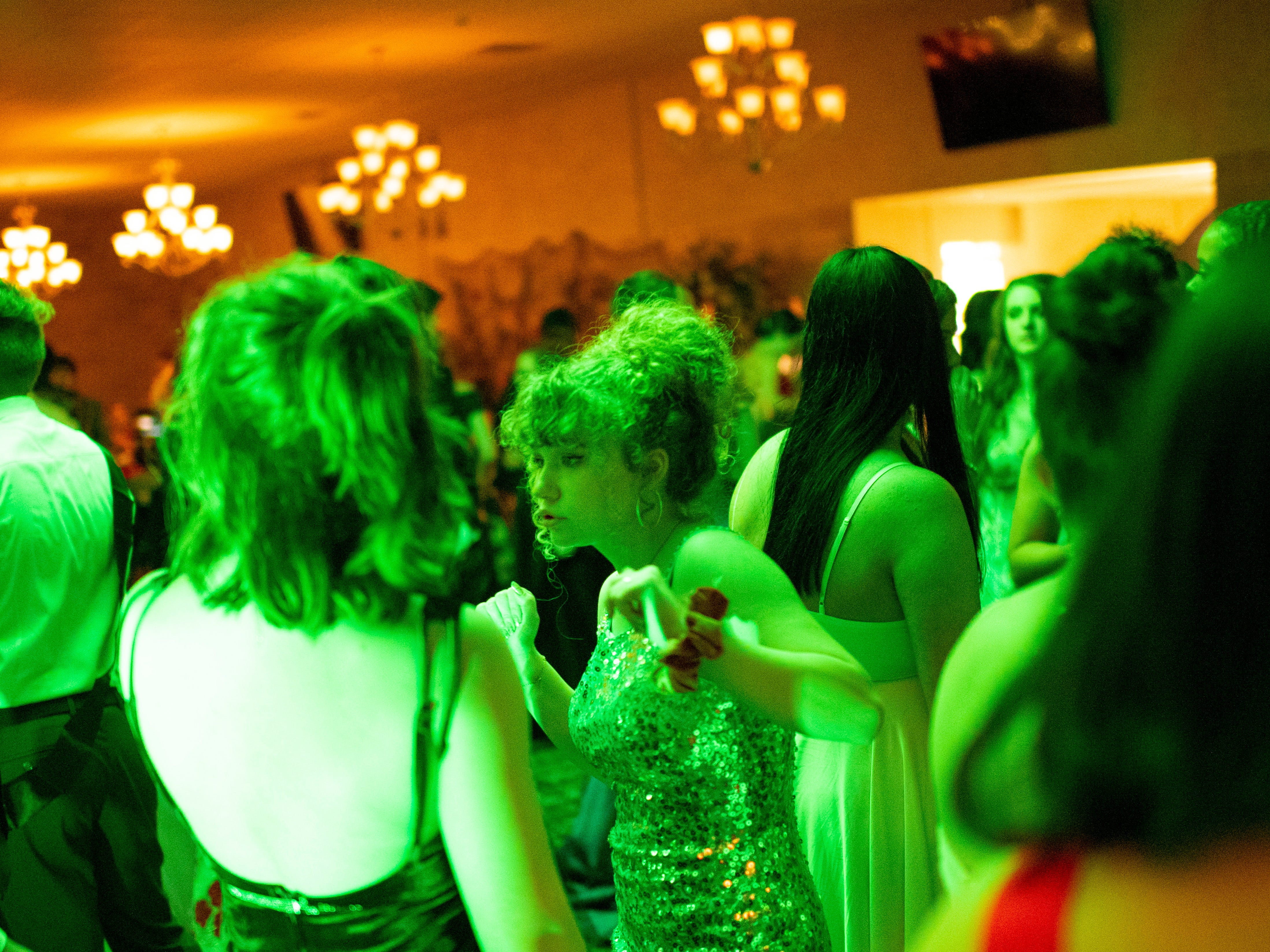 """Kirstin Brust, 17, center, and Nicole Kobylanski, 17, left, dance at """"Jurassic Prom"""" at Party Central Saturday night."""