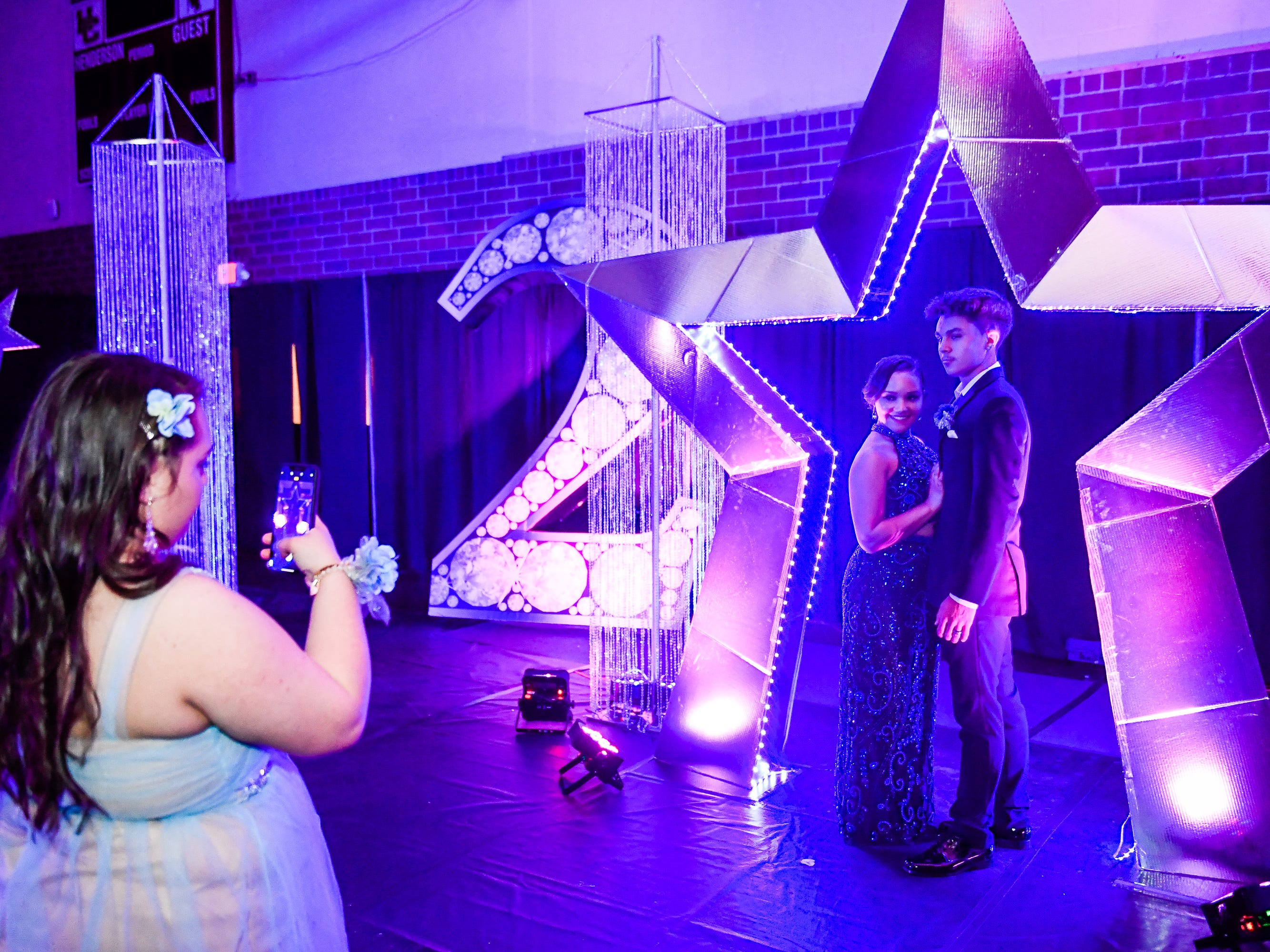 Skyler Kalley takes Alexsia Savage and Gabrial Clary's picture in the star at the Henderson County High Prom held at Colonel Gym Saturday, April 13, 2019.