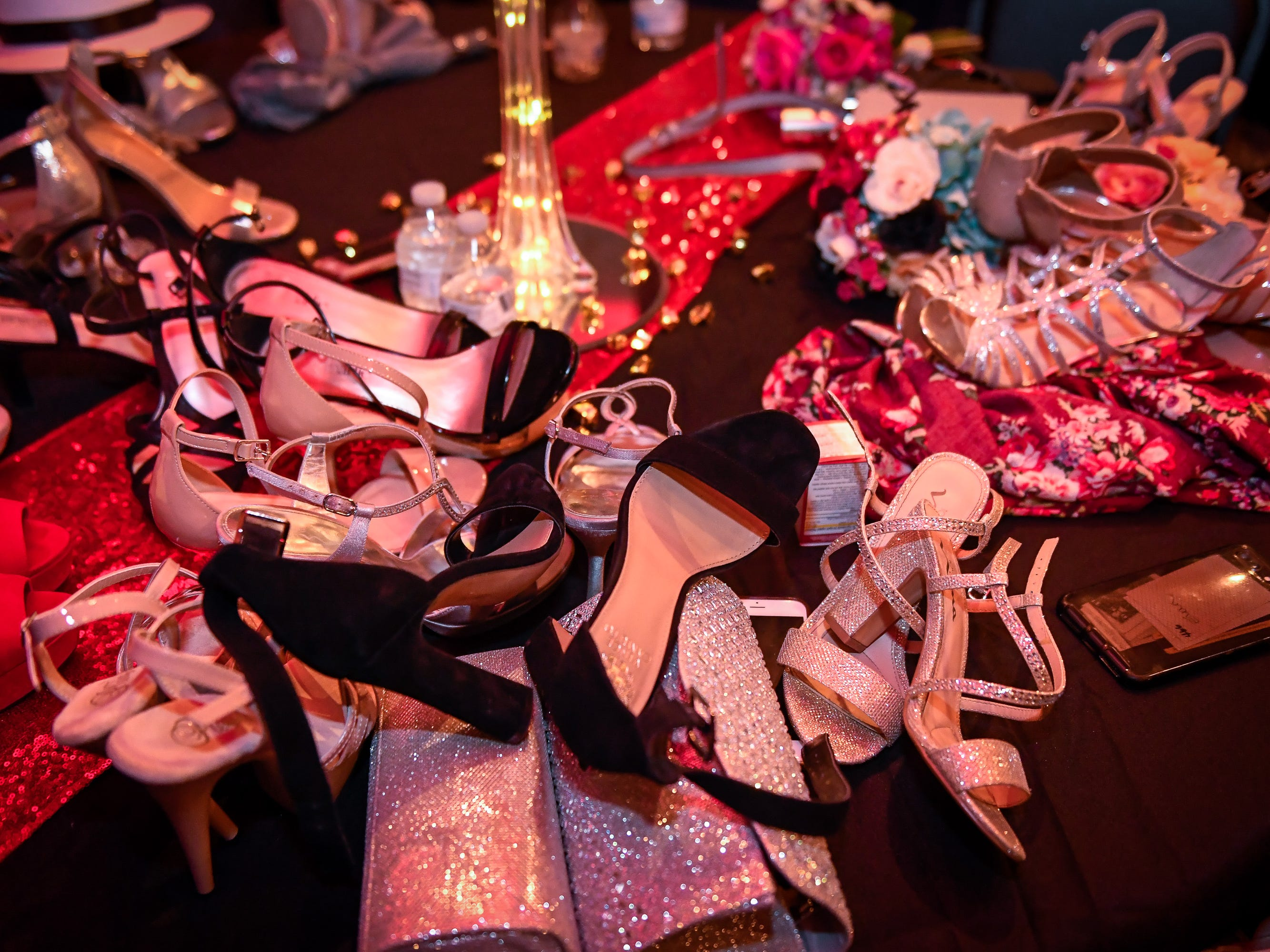 Shoes cover a table as couples head to the dance floor at the North High School Prom held at the Old Post Office in downtown Evansville Saturday, April 13, 2019.