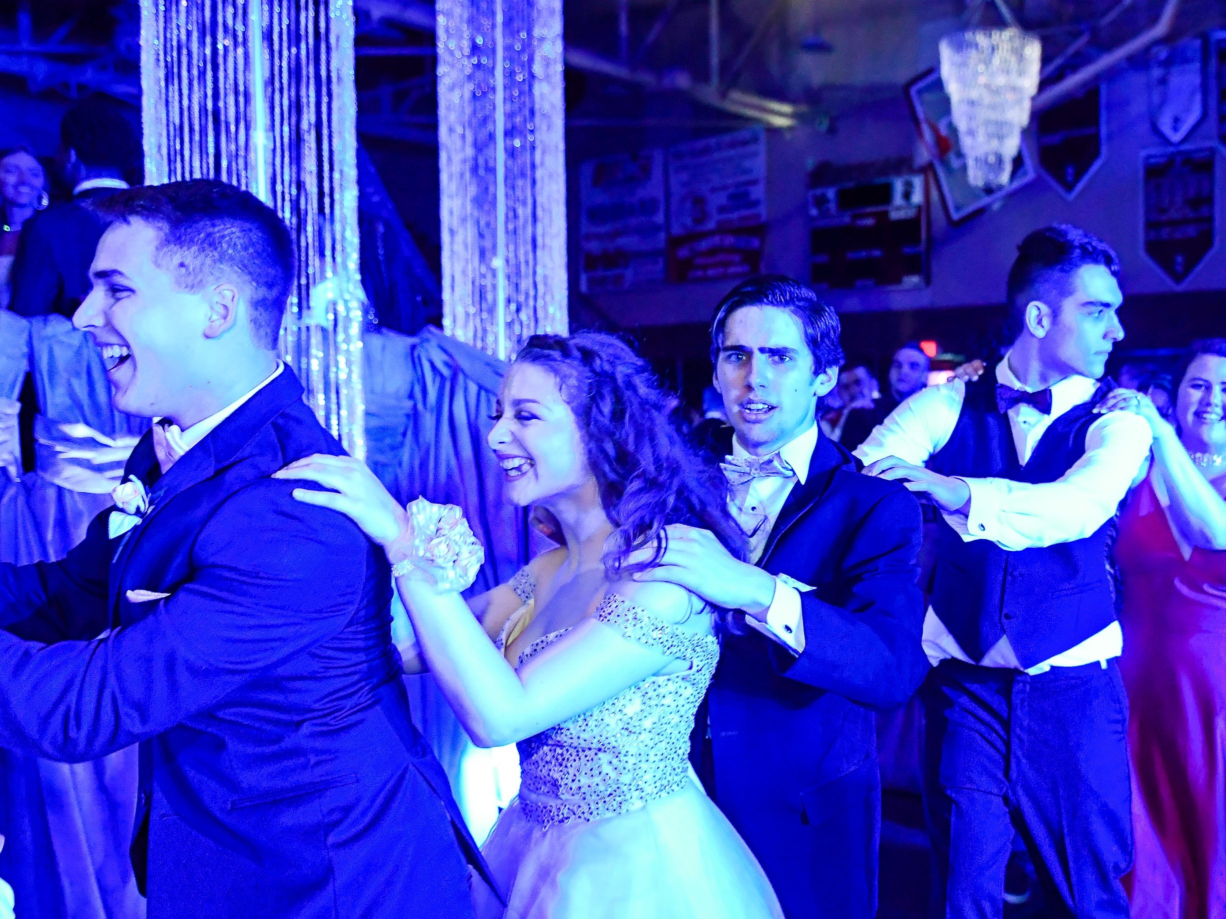 A Conga line winds its way through the dance floor at the Henderson County High Prom held at Colonel Gym Saturday, April 13, 2019.