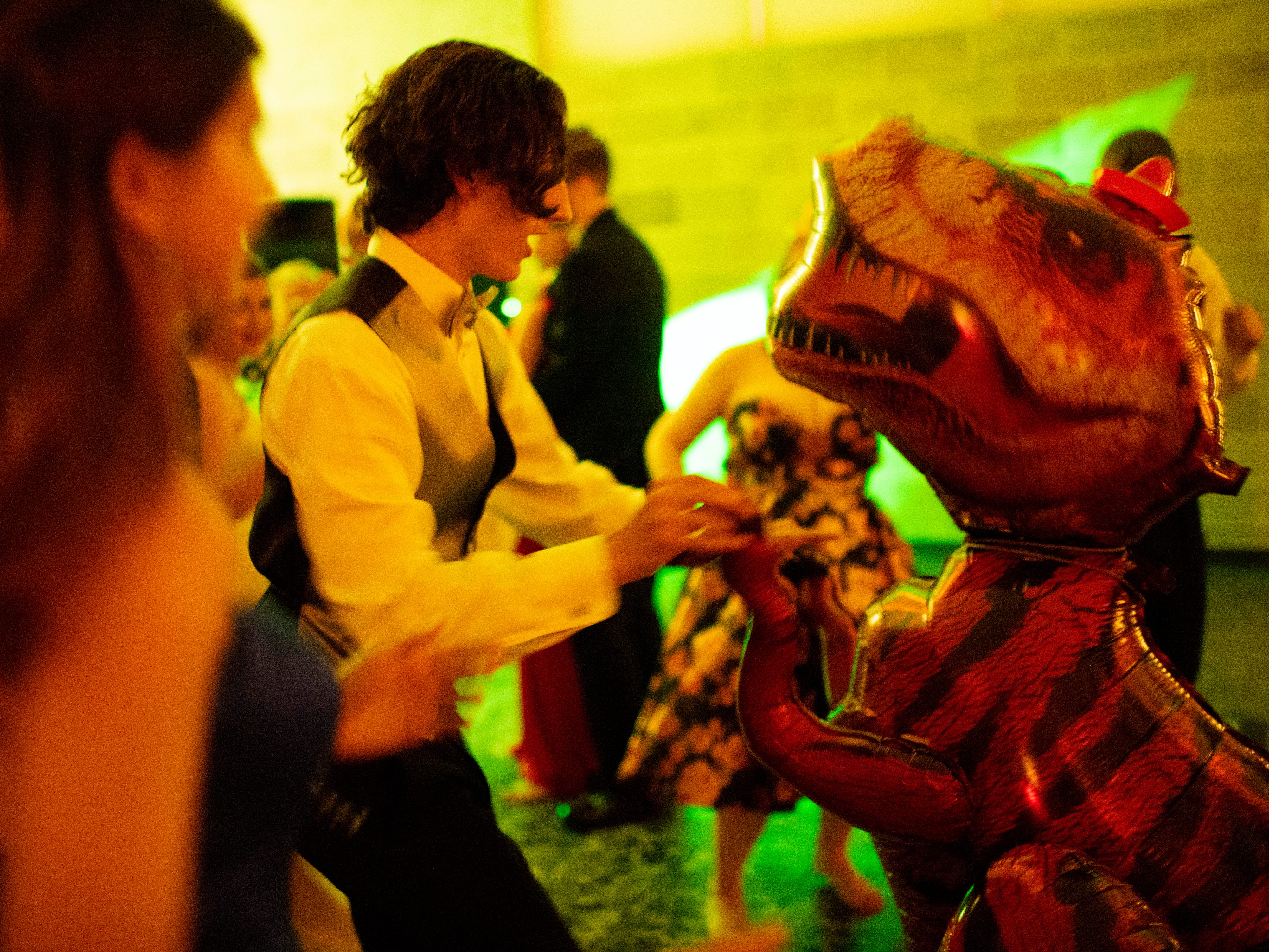 """Signature School senior Michael Line dances with an inflatable T-rex at """"Jurassic Prom"""" at Party Central Saturday night."""