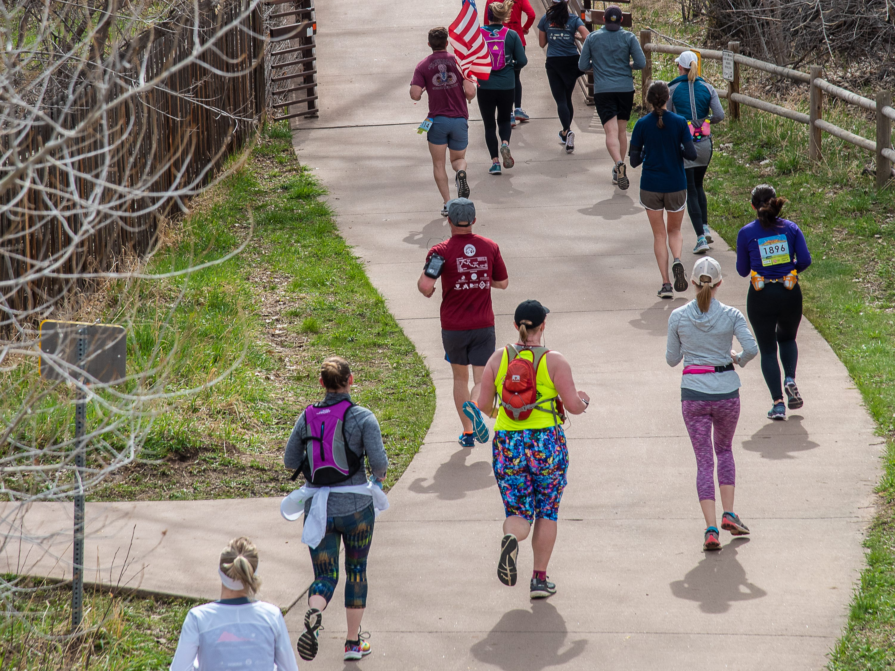 Participants enter the Poudre Trail east of Lyons Park during the Horsetooth Half Marathon on Sunday, April 14, 2019, in Fort Collins, Colo.