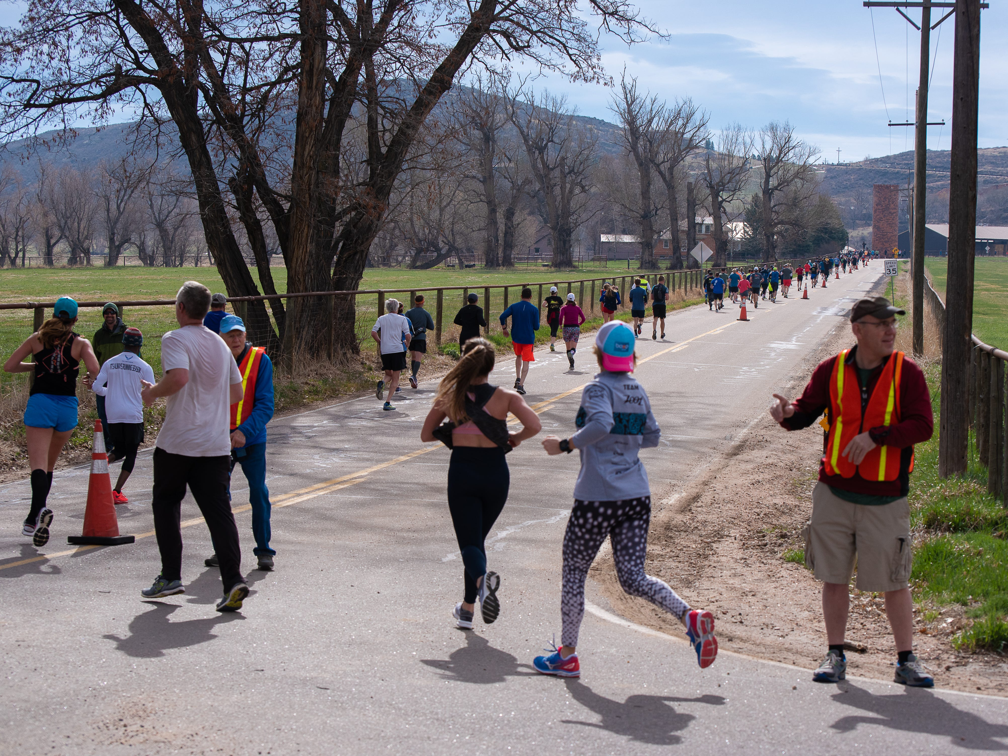 Participants round a turn and head east on Bingham Hill Road during the Horsetooth Half Marathon on Sunday, April 14, 2019, in Fort Collins, Colo.