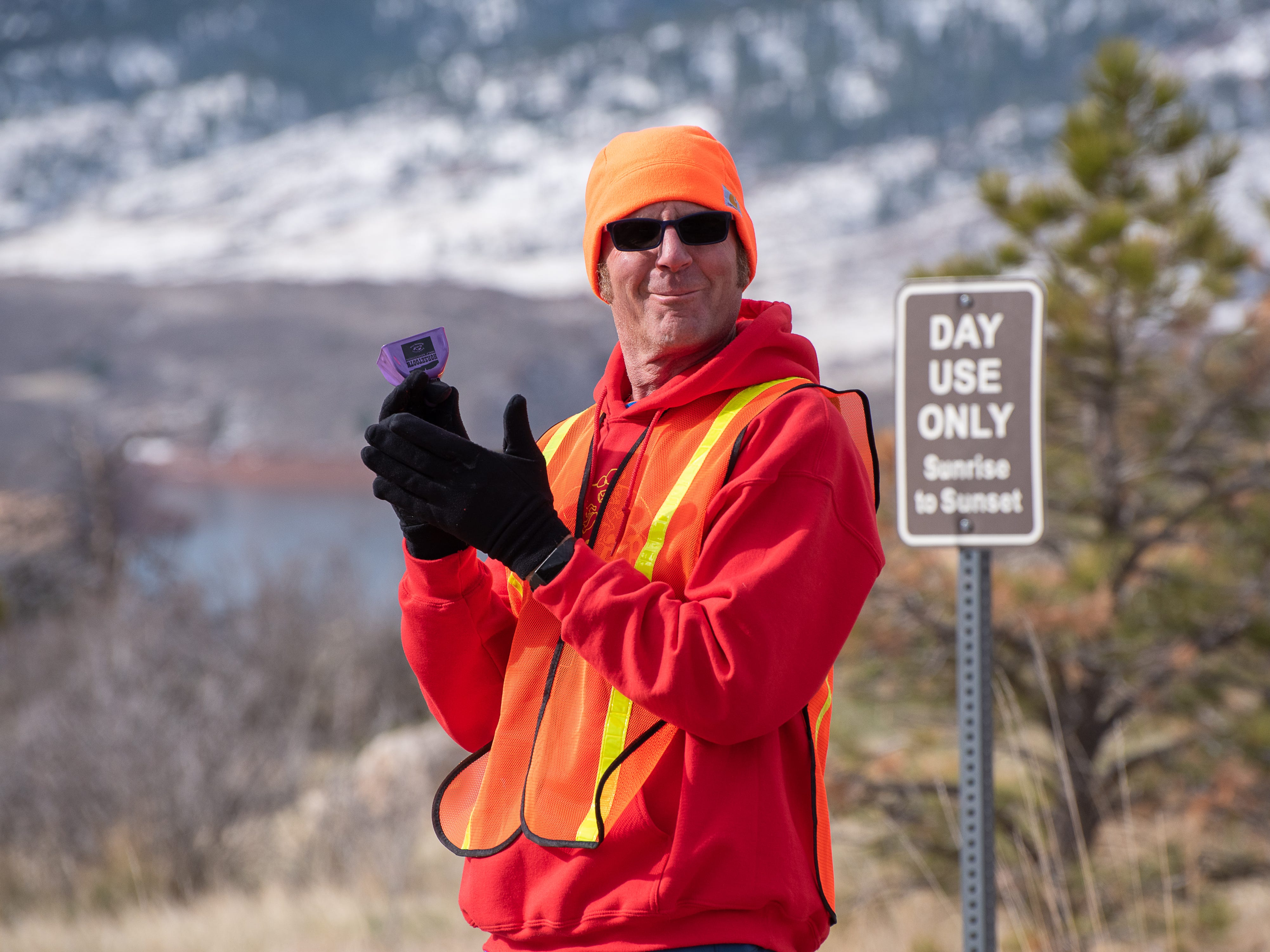 A race volunteer cheers on runners during the Horsetooth Half Marathon on Sunday, April 14 2019, in Fort Collins, Colo.