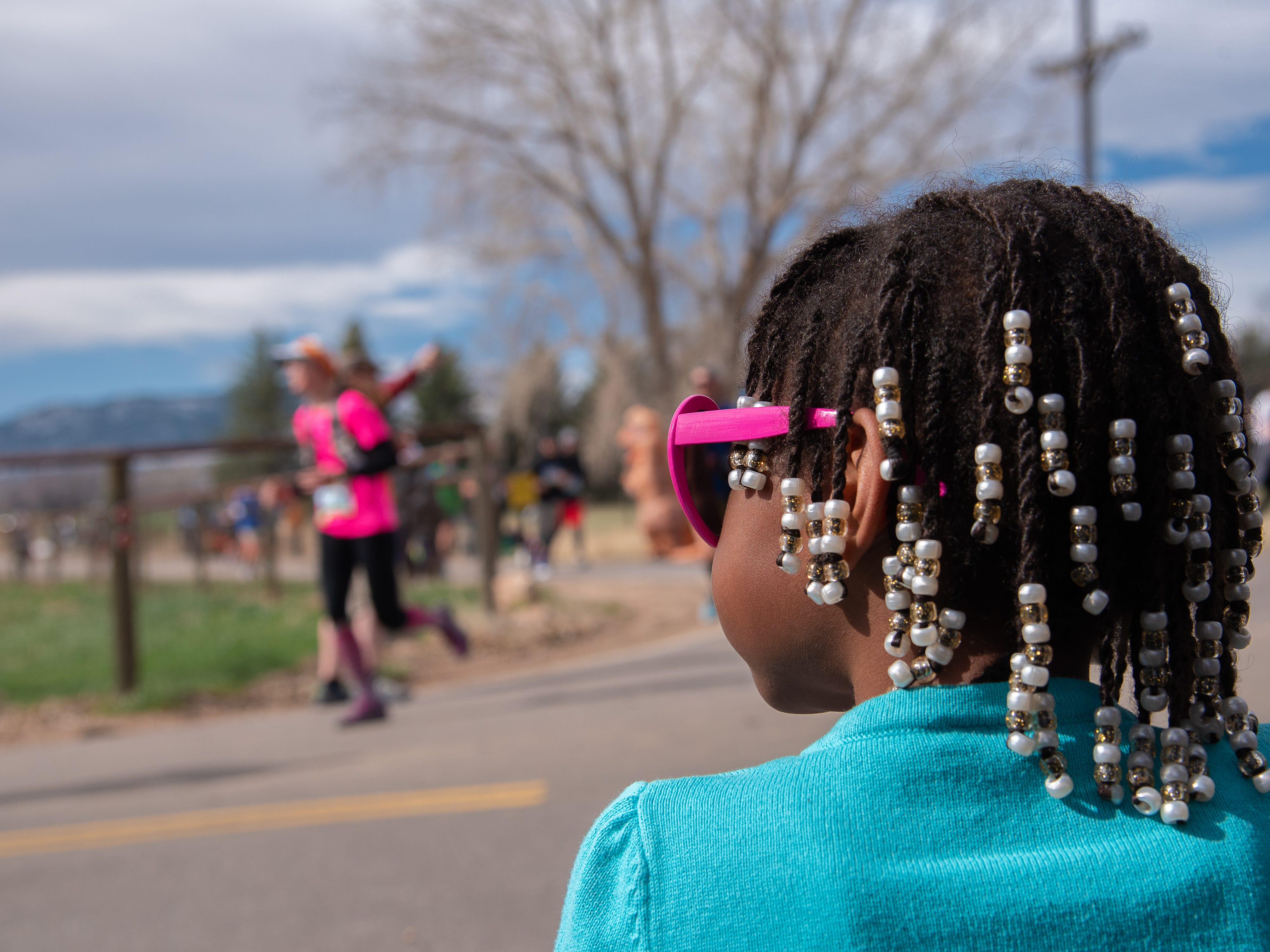 Samantha Benson, 6, watches race participants make a turn and head east on Bingham Hill Road during the Horsetooth Half Marathon on Sunday, April 14, 2019, in Fort Collins, Colo.