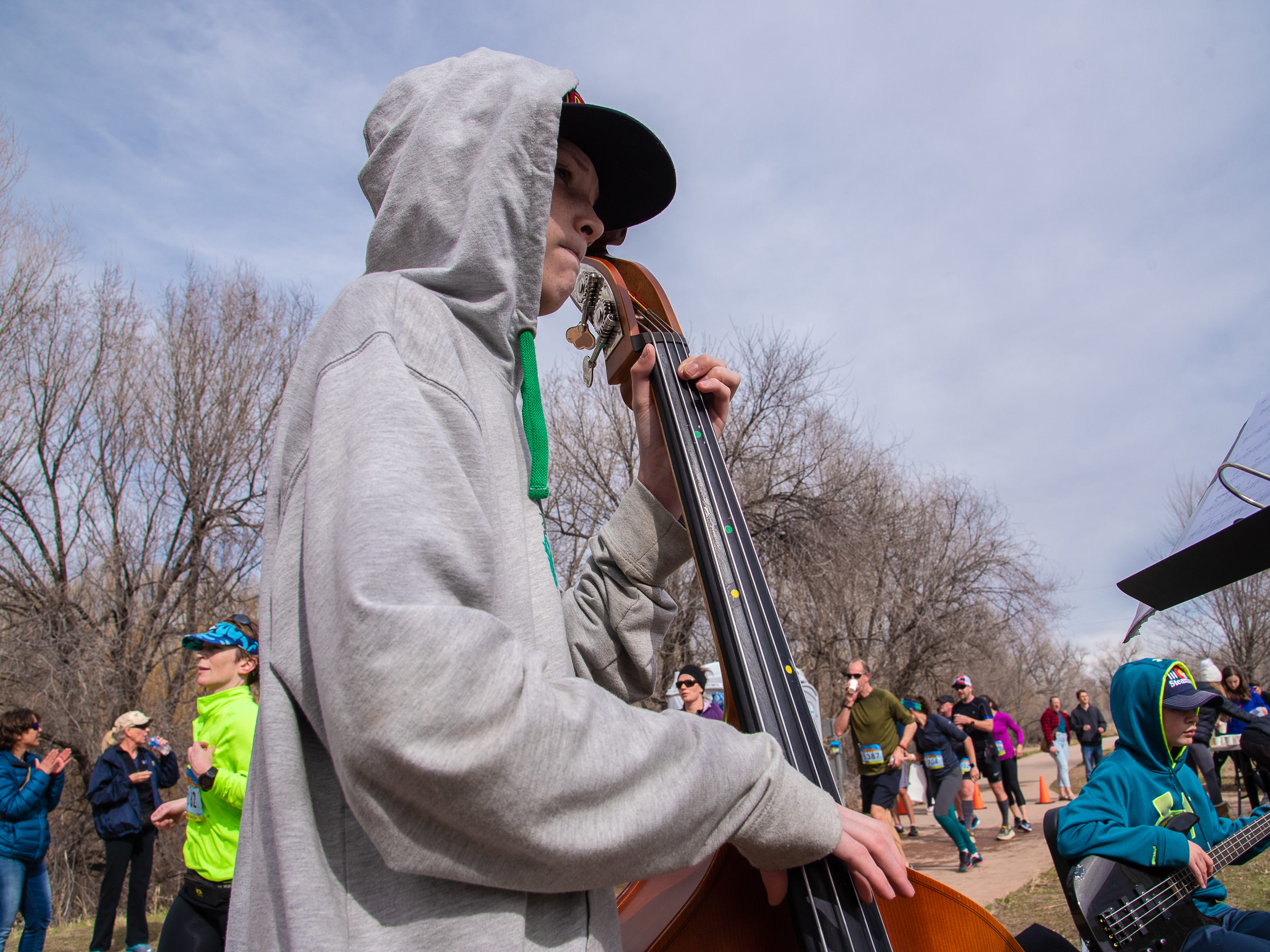 Participants pass through Lyons Park during the Horsetooth Half Marathon on Sunday, April 14, 2019, in Fort Collins, Colo. The Blevins Middle School Jazz Band entertained runners as they passed by a first aid station.