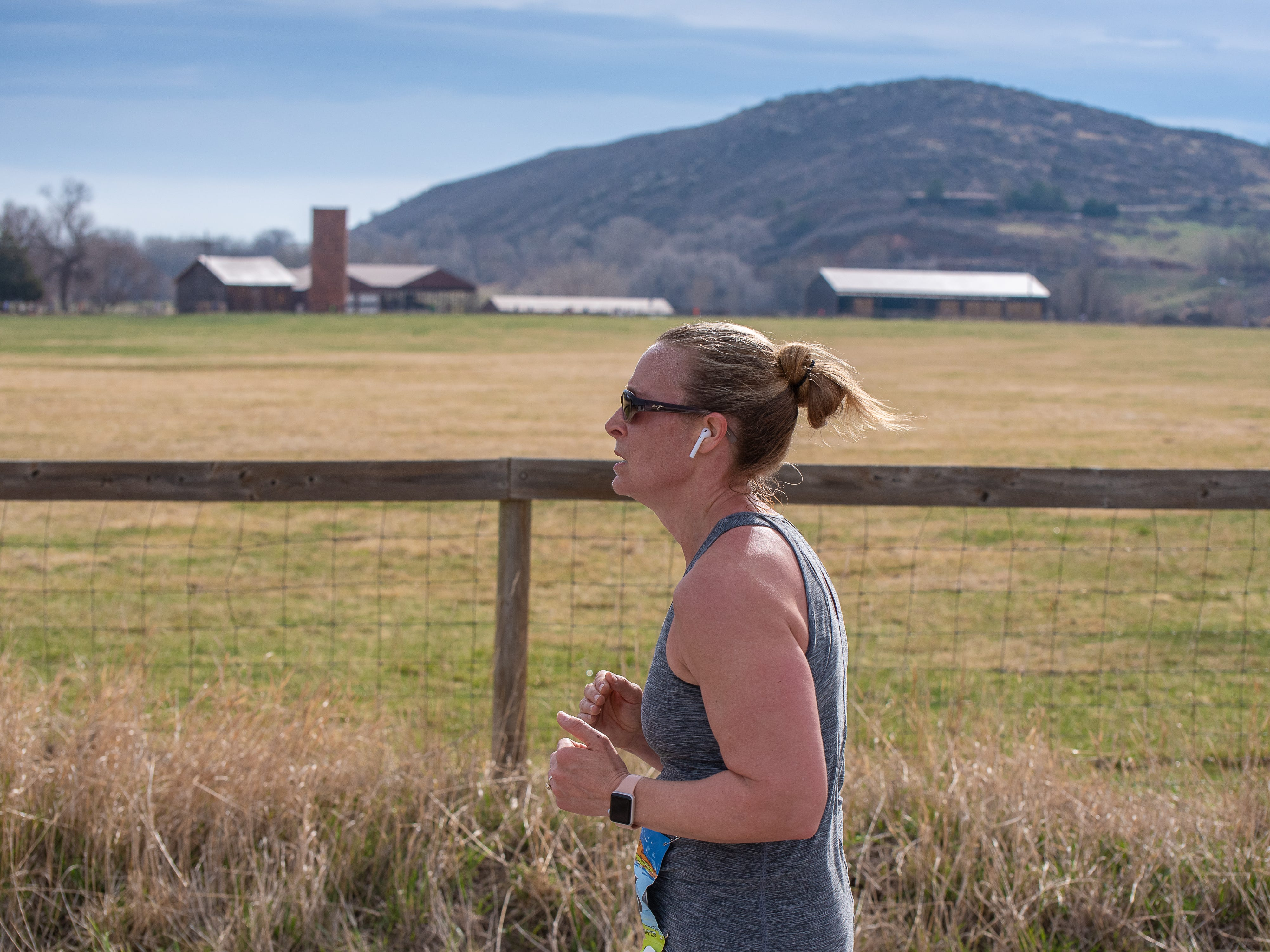 A participant runs by an open field near Bellvue during the Horsetooth Half Marathon on Sunday, April 14 2019, in Fort Collins, Colo.