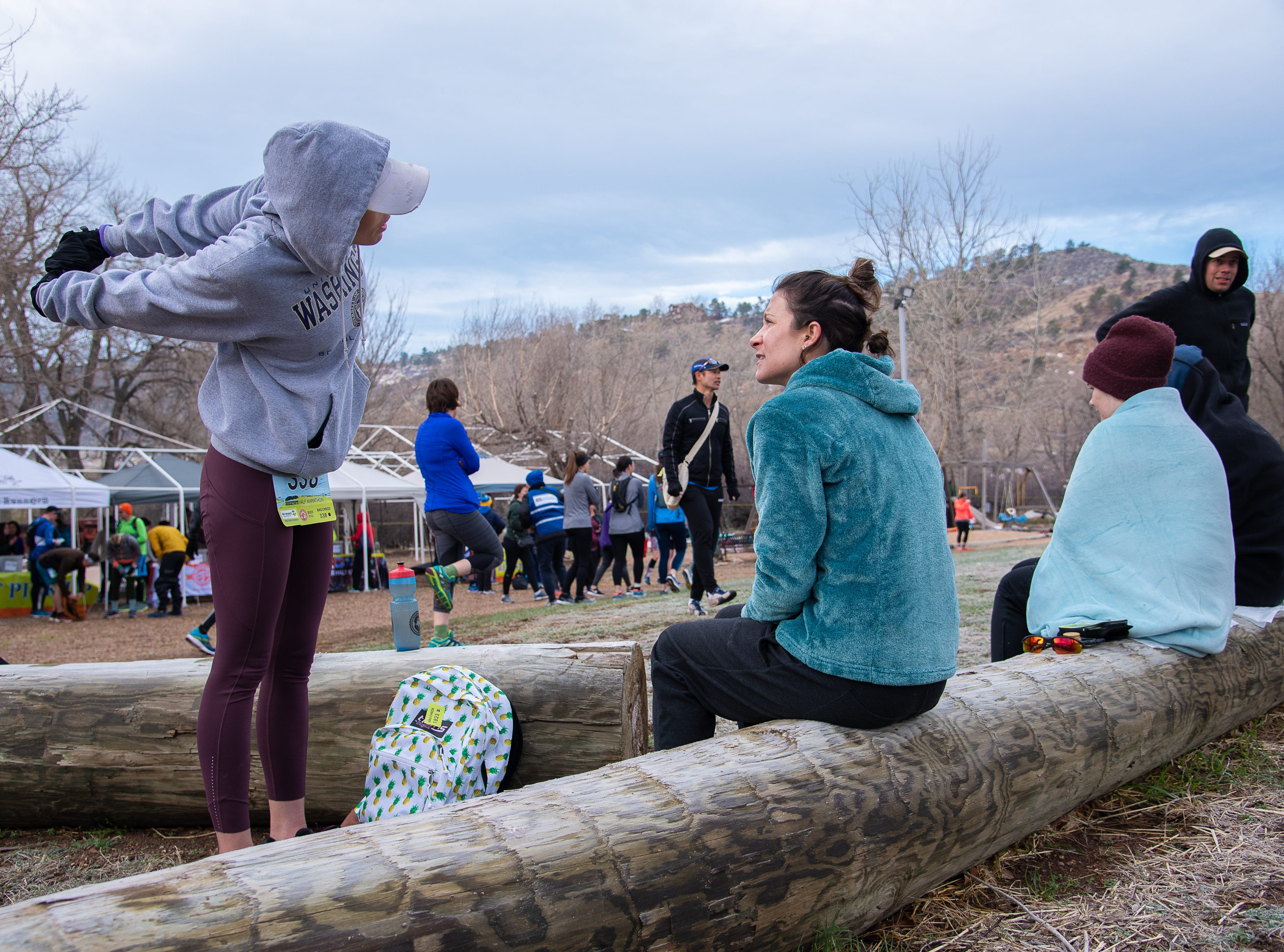 Participant Amanda Smylie limbers up as she speaks with Allie Oban before the start of the Horsetooth Half Marathon on Sunday, April 14, 2019, in Fort Collins, Colol