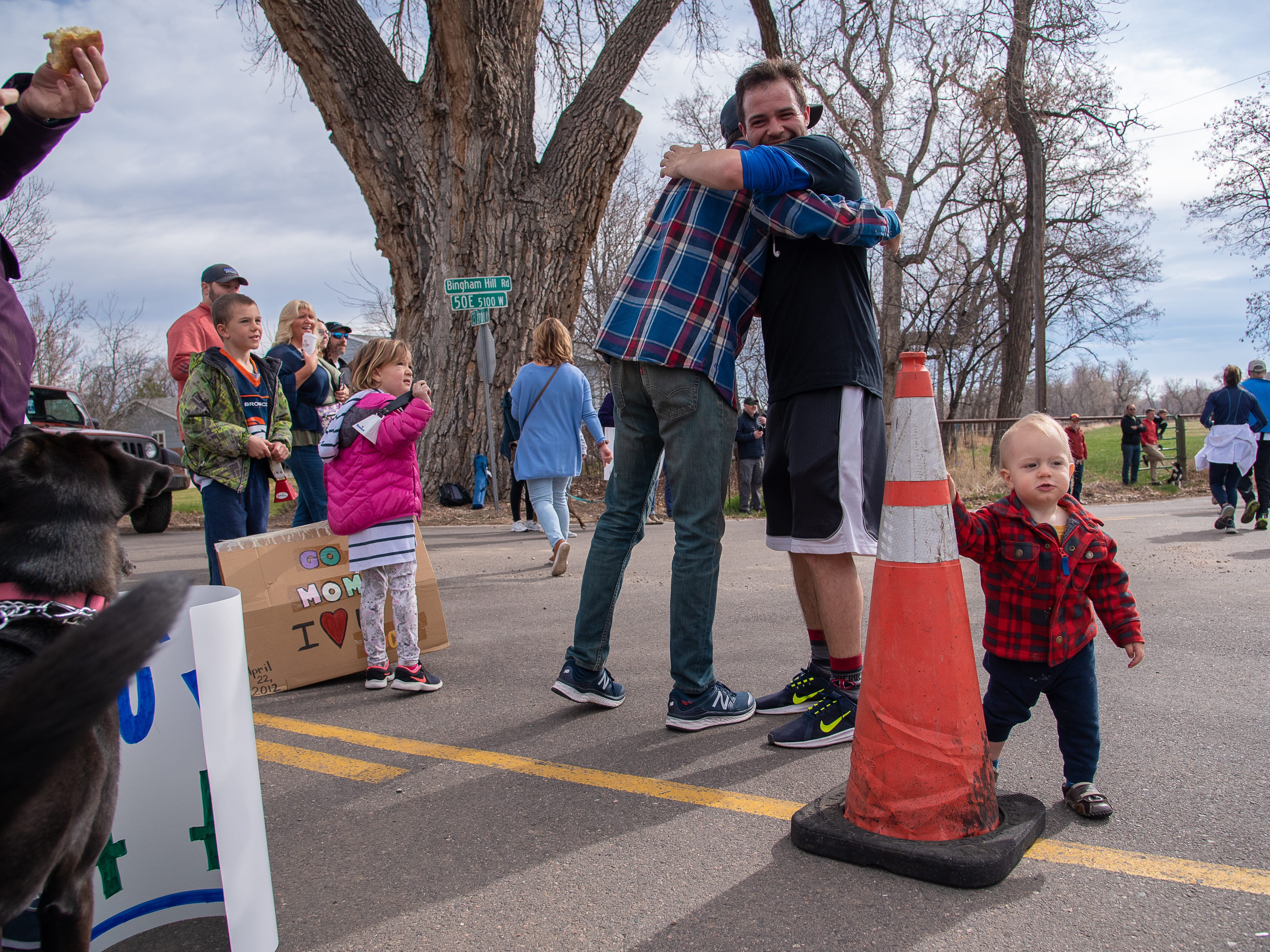Jude Veliquette, 1, holds a safety cone and watches race participants near the corner of Bingham Hill Road during the Horsetooth Half Marathon on Sunday, April 14, 2019, in Fort Collins, Colo.