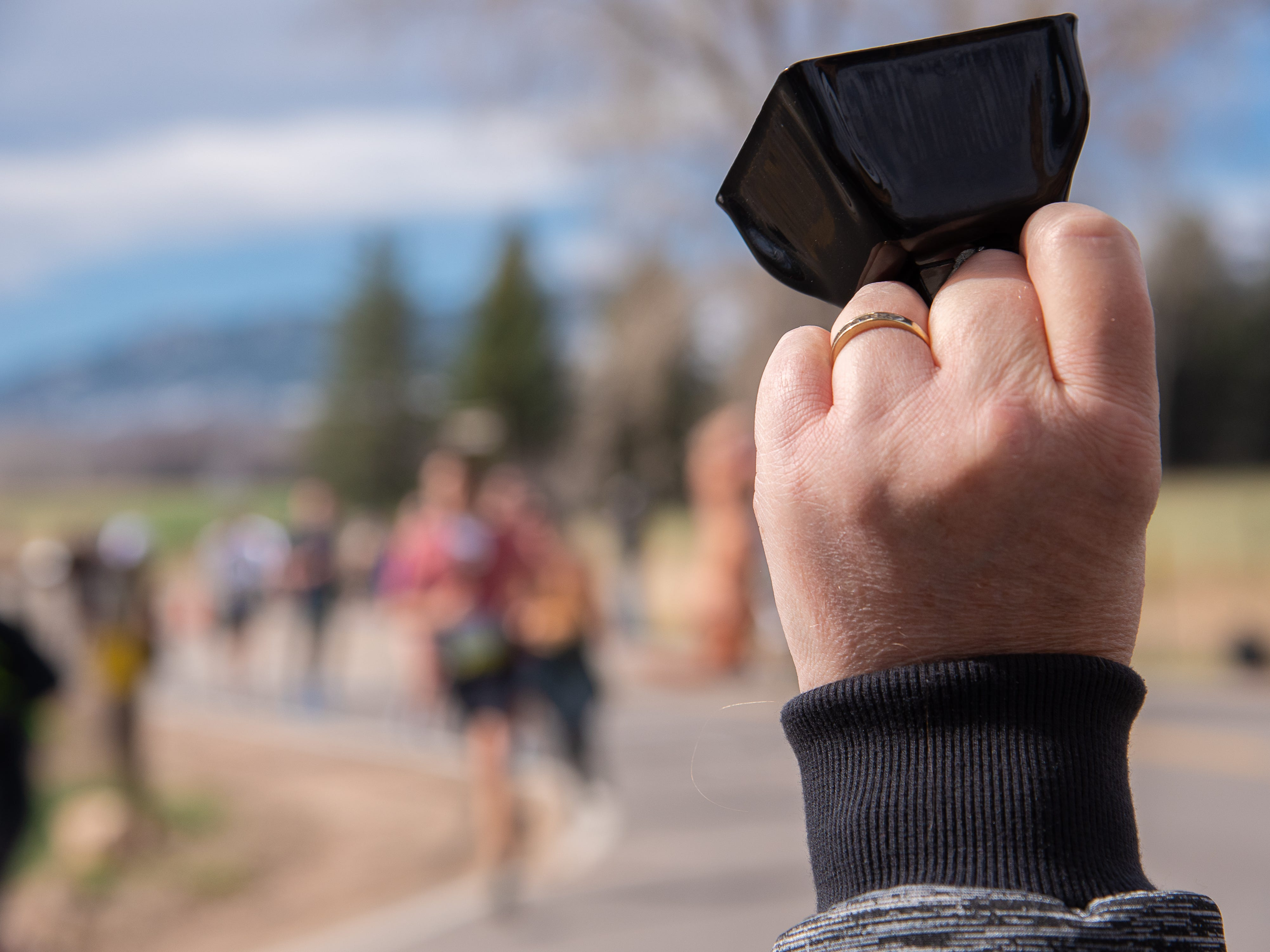 A spectator rings a cowbell in support of race participants near Bingham Hill Road during the Horsetooth Half Marathon on Sunday, April 14, 2019, in Fort Collins, Colo.